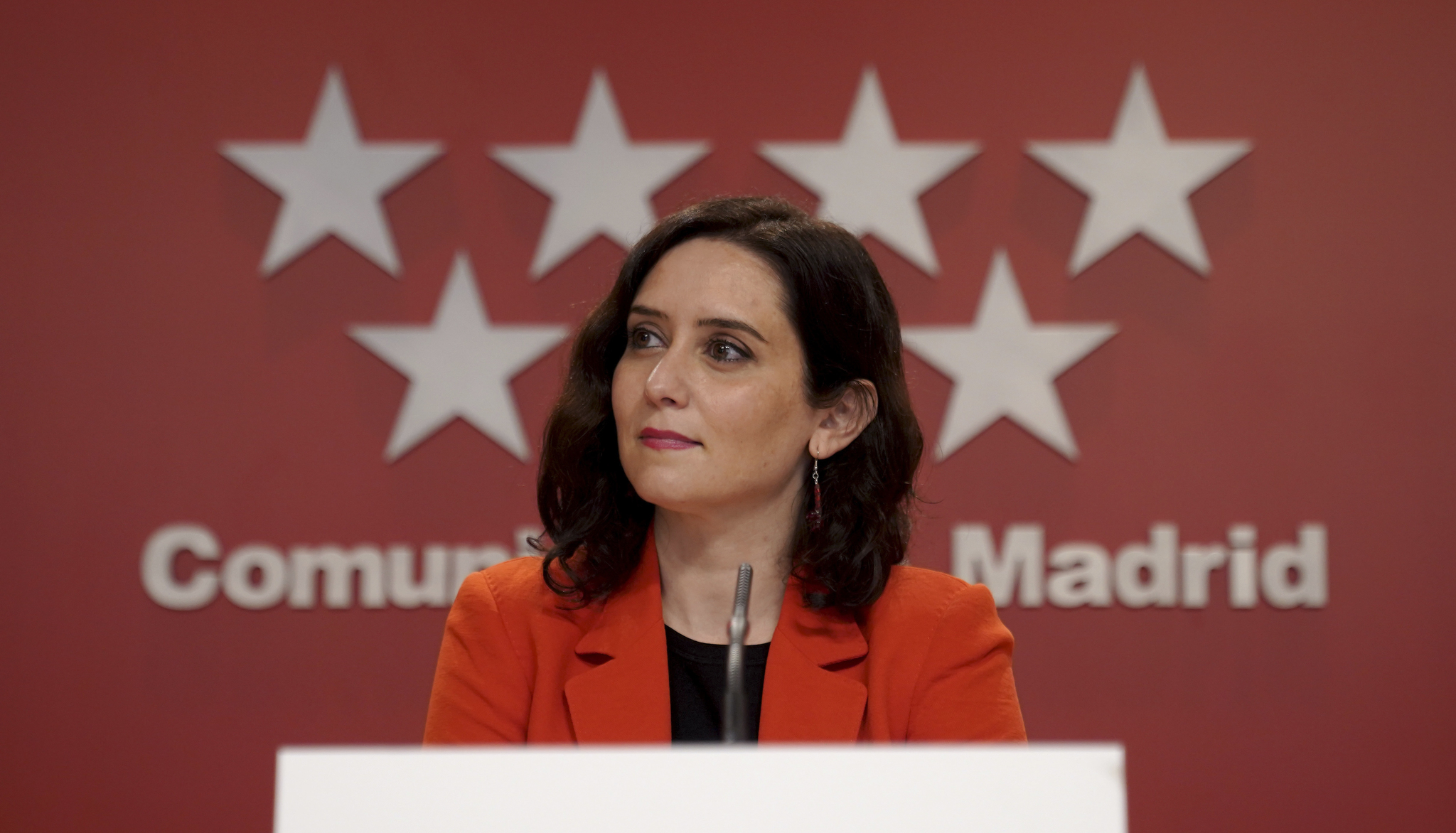 Isabel Díaz Ayuso tras la bandera de la comunidad