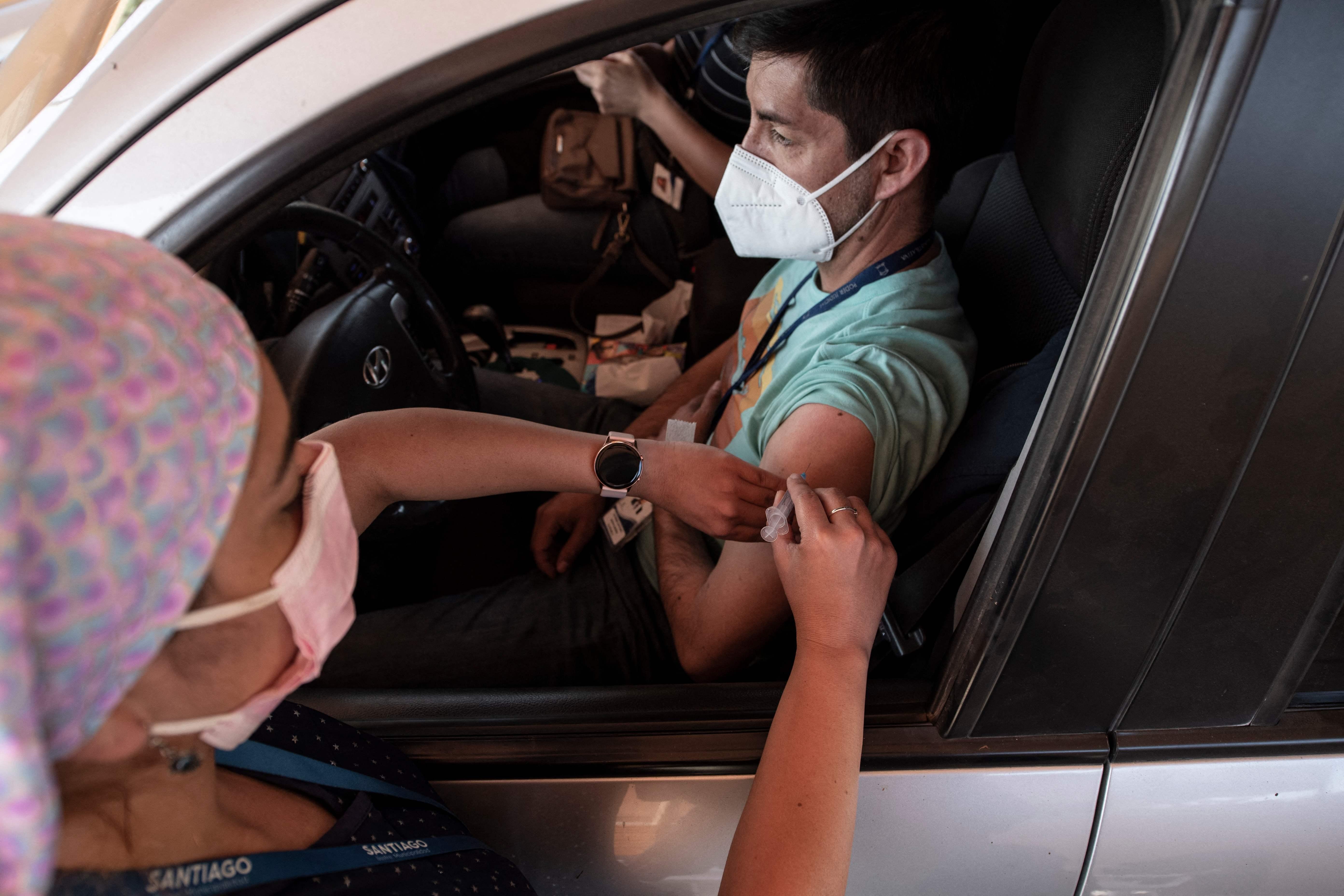 Un chileno recibe la vacuna china desde su vehículo.