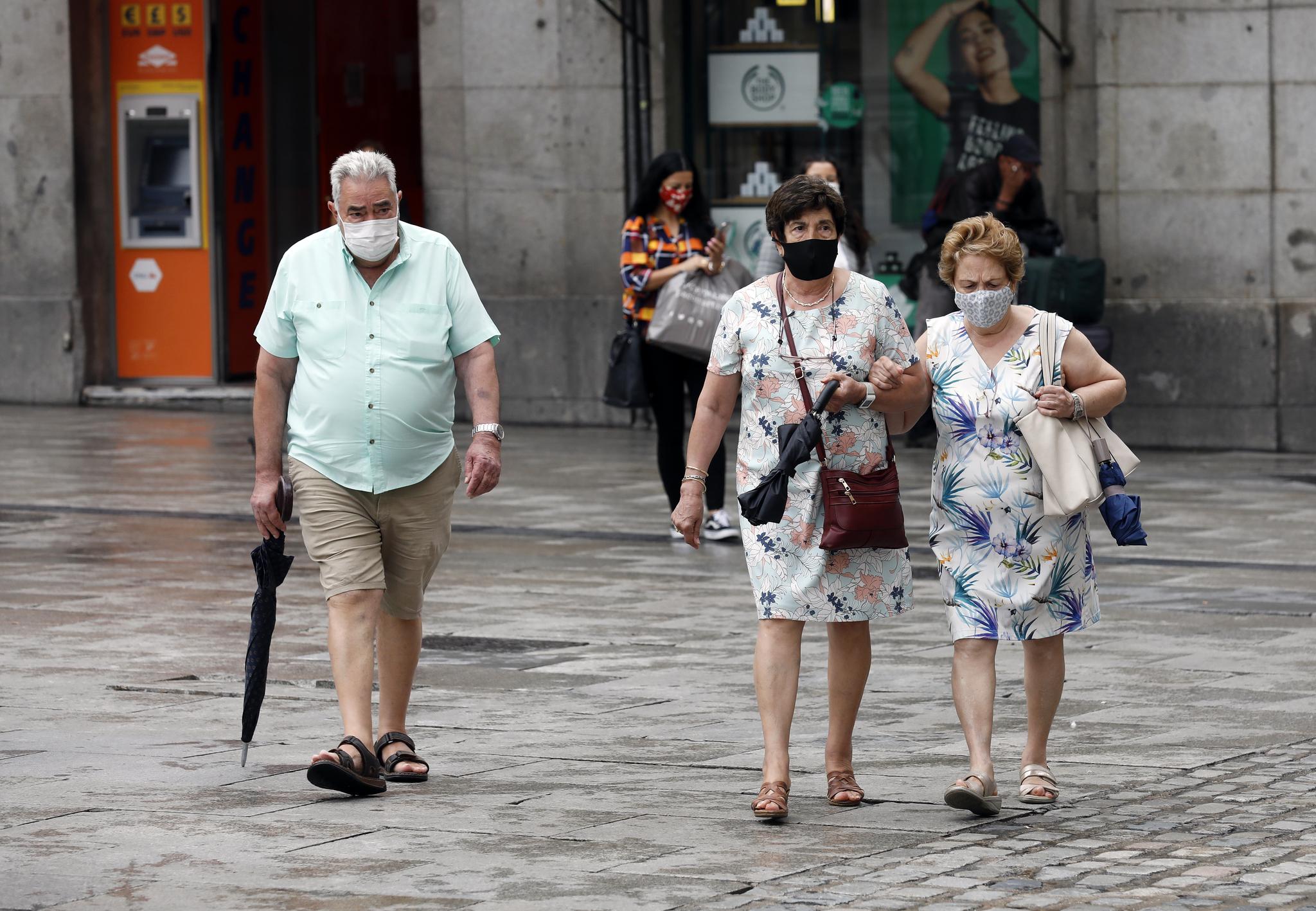 Tres personas mayores en la Puerta del Sol de Madrid.