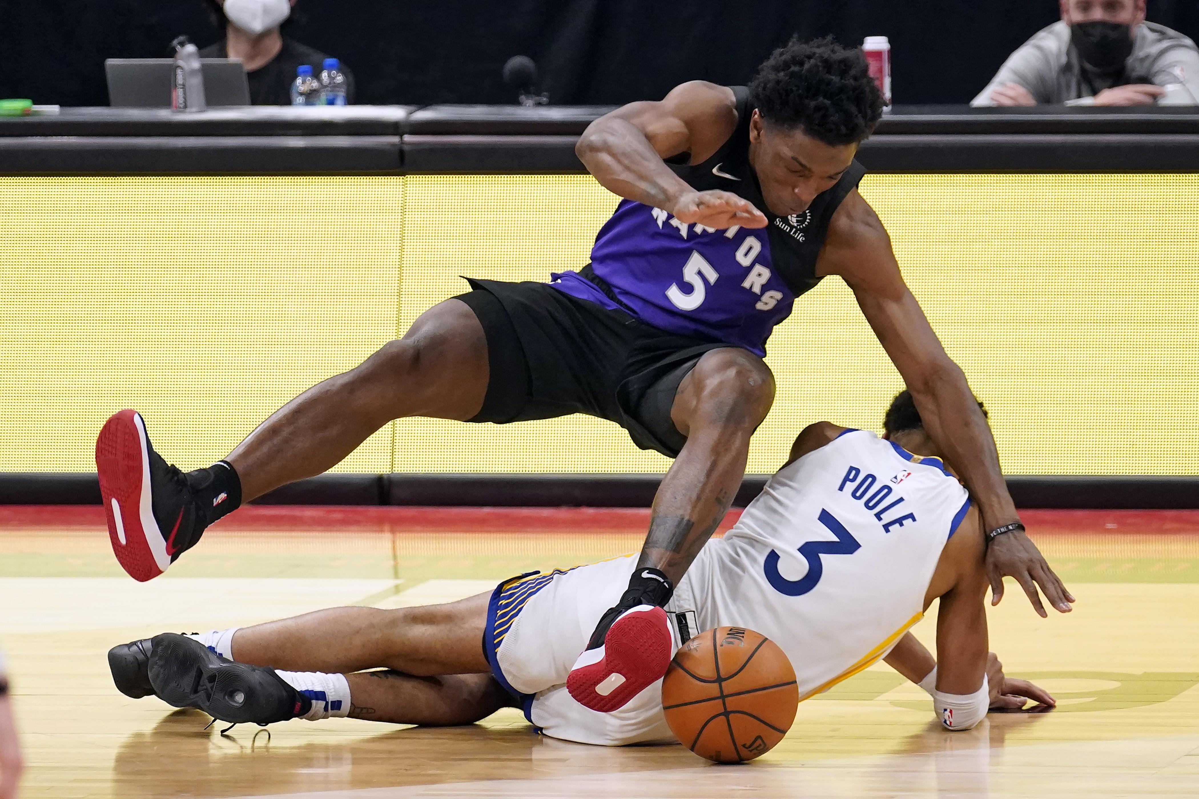 Stanley Johnson, de los Raptors, cae sobre el jugador de los Warriors Jordan Poole.