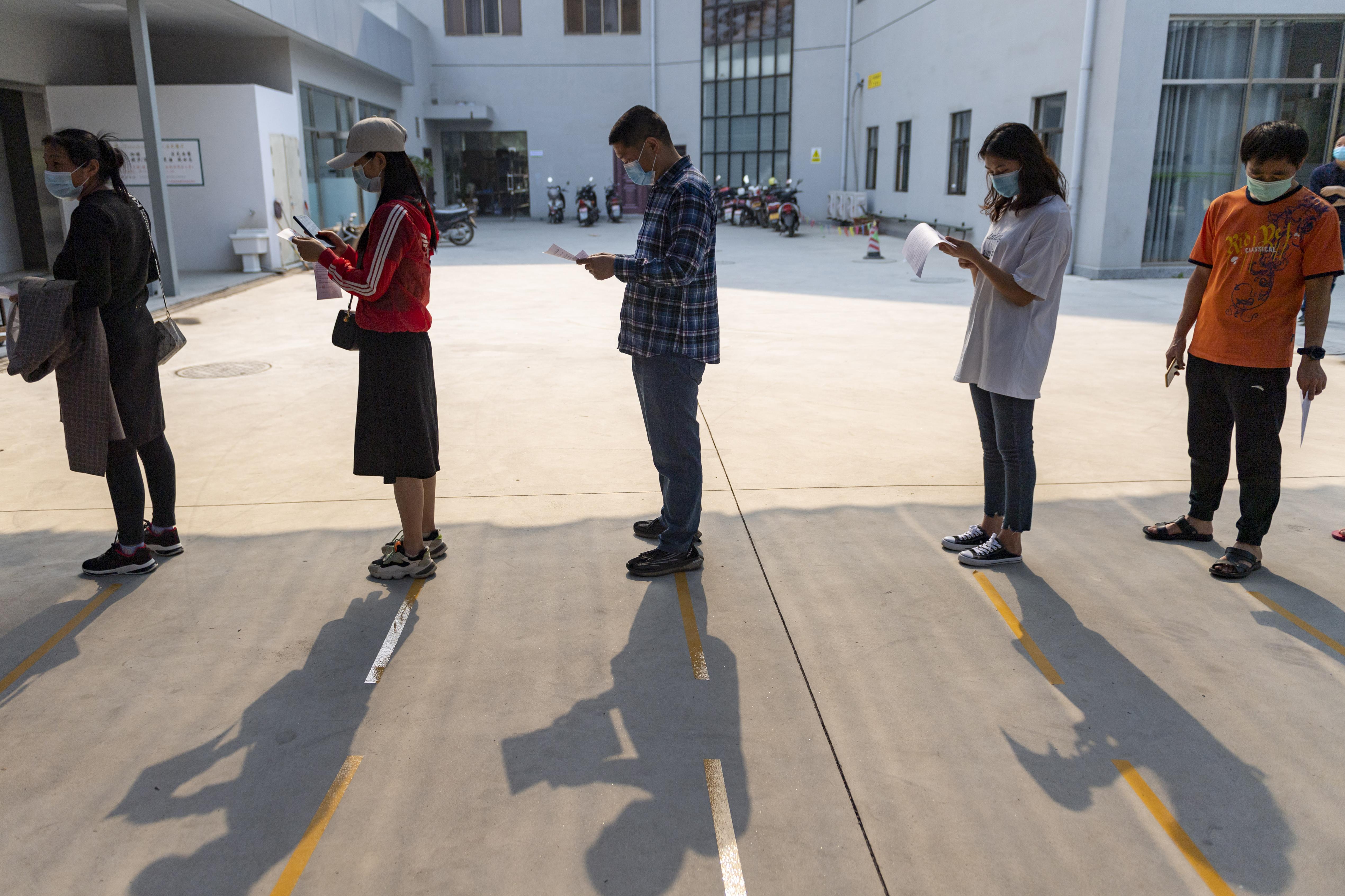 Personas en fila para recibir la vacuna contra el Covid en Ruili, China.