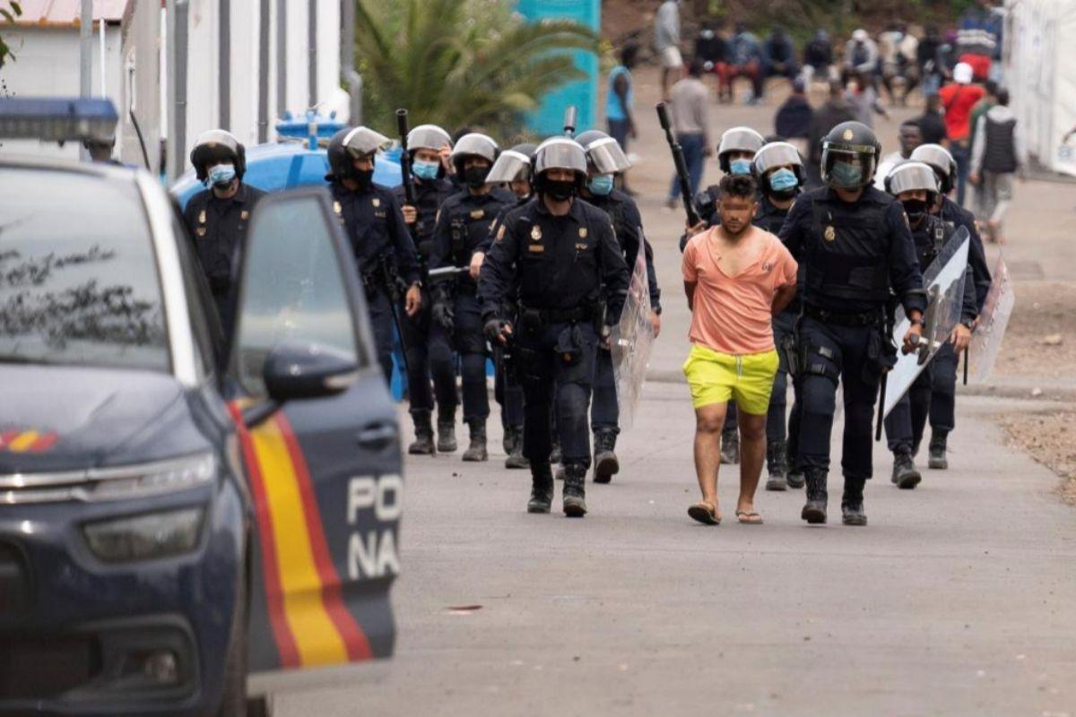 Agentes policiales trasladan a una de las personas detenidas.