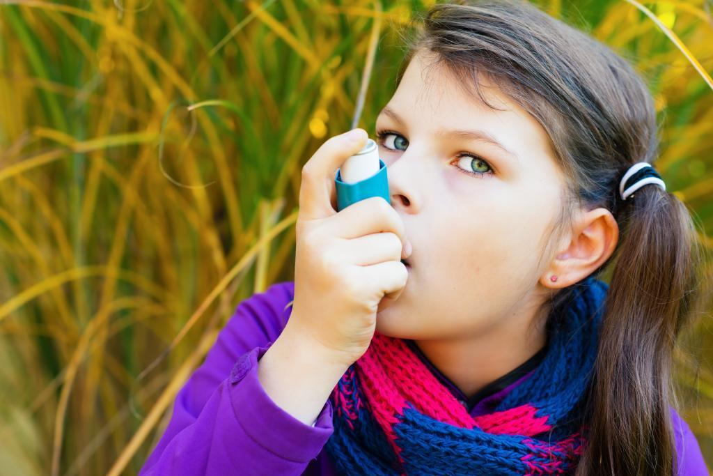 Una niña utiliza un inhalador contra la alergia.