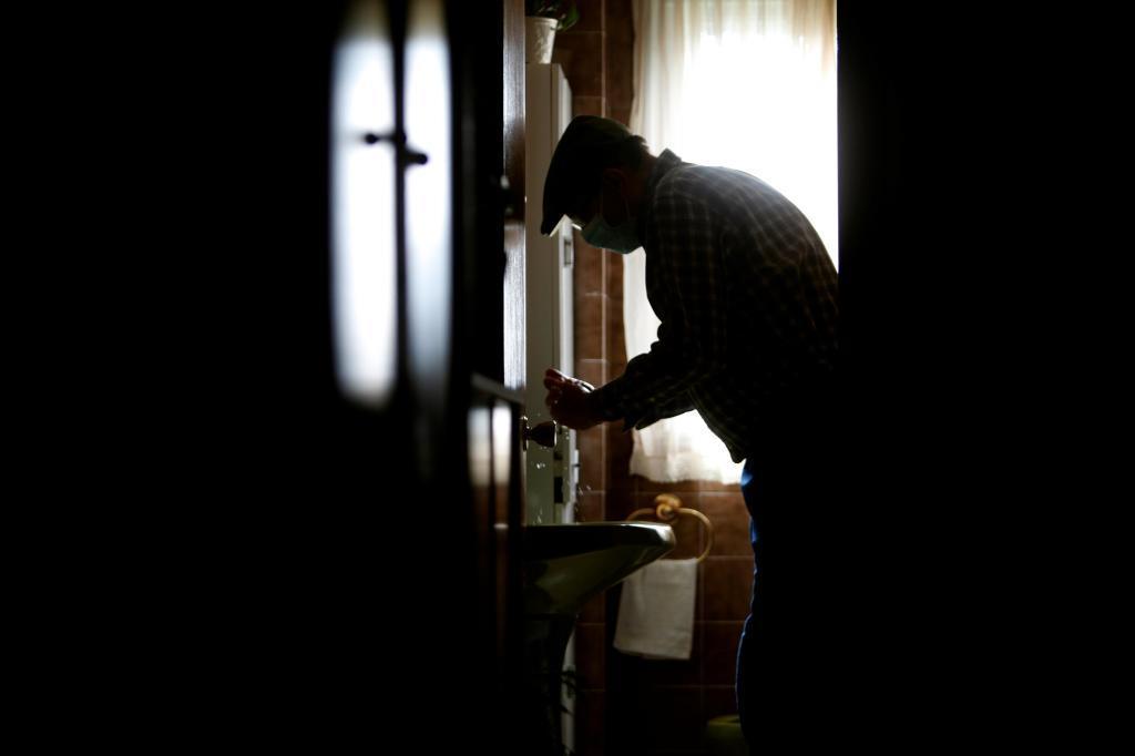 Un anciano se lava las manos en su casa del concello coruñés de Pontedeume.