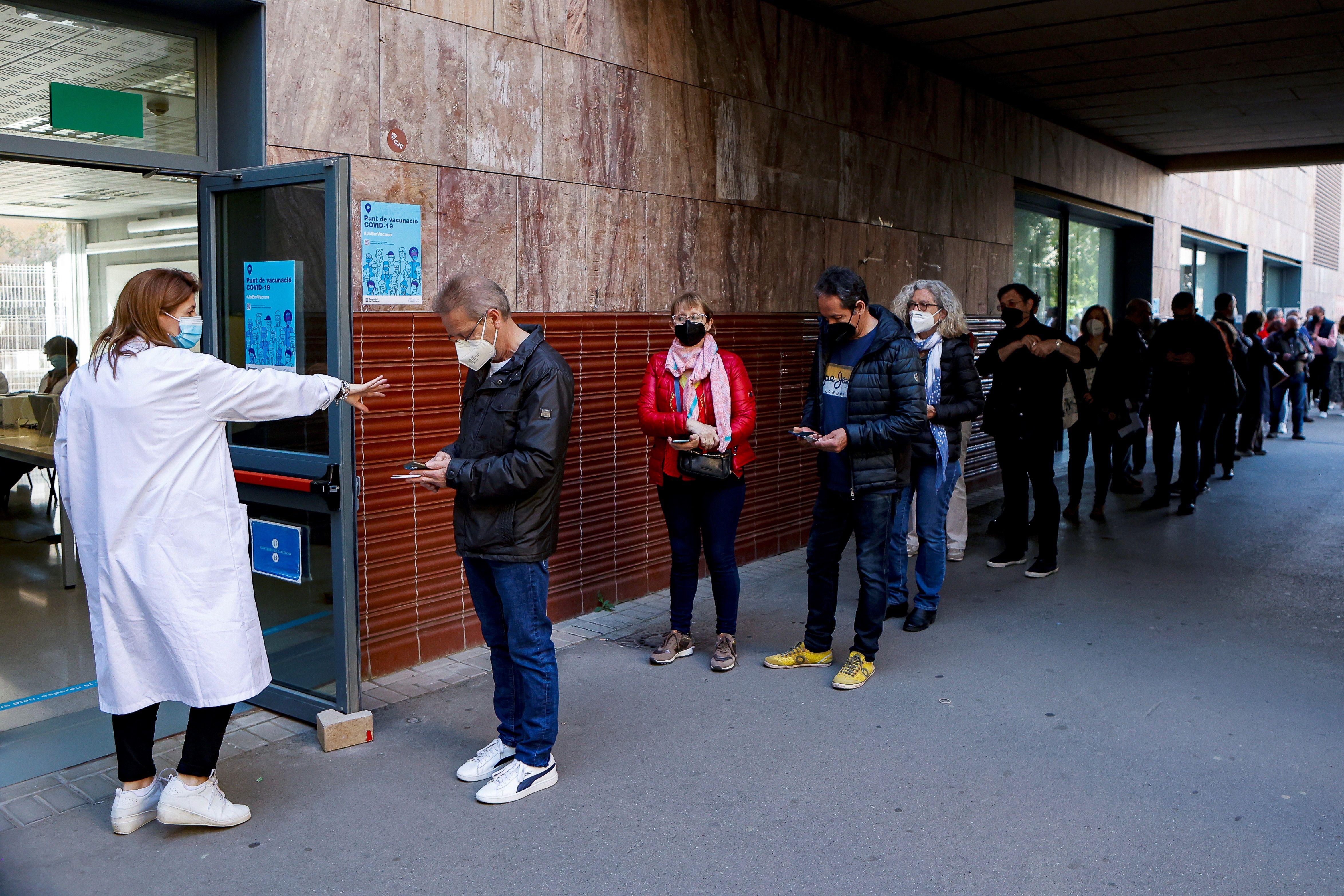 Varias personas hacen cola en un centro de vacunación de Barcelona.
