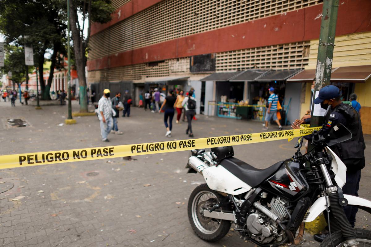 Un policía precinta el acceso a un mercado, en Caracas.