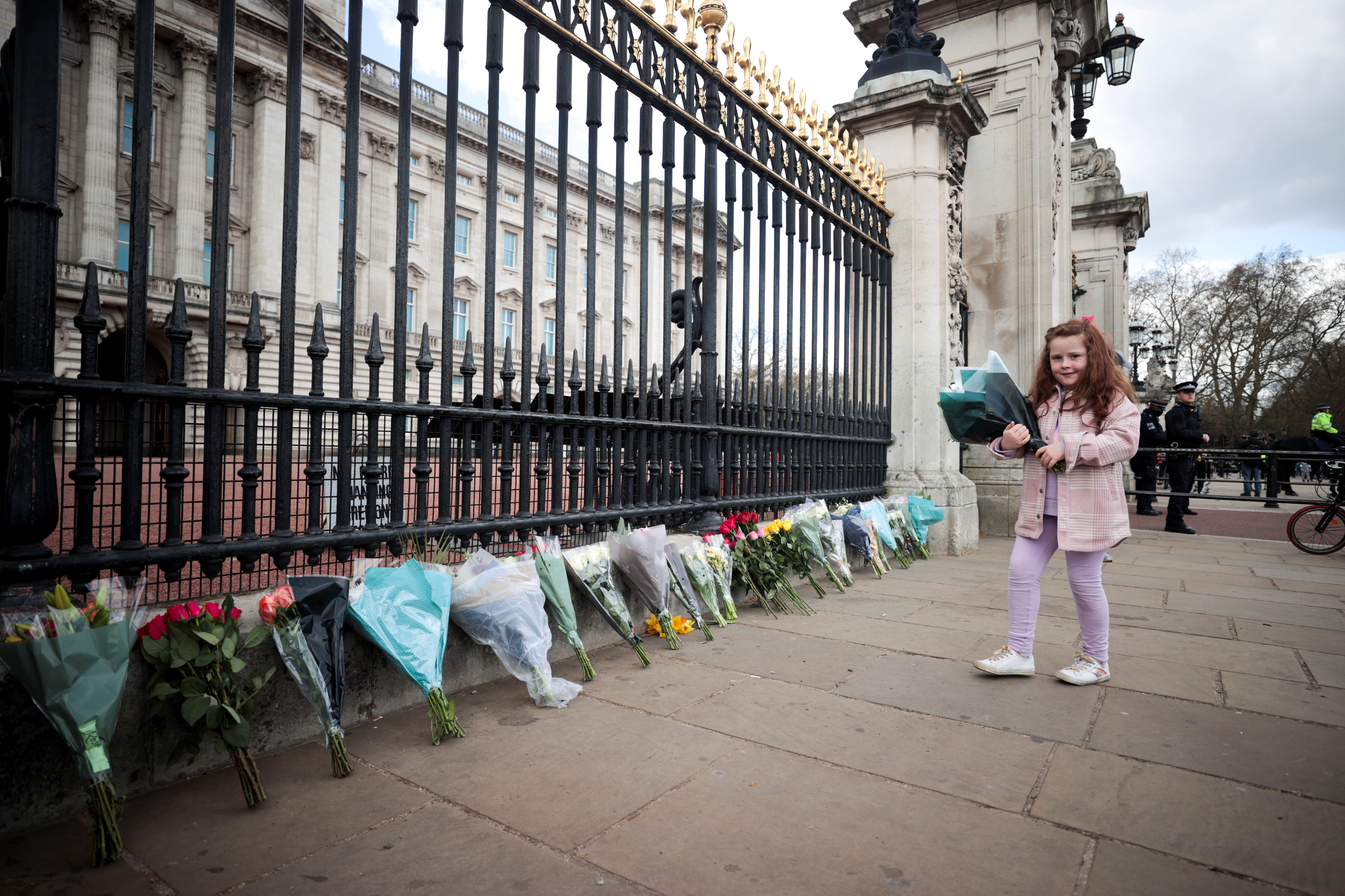 Una niña deja flores en el palacio de Buckingham.