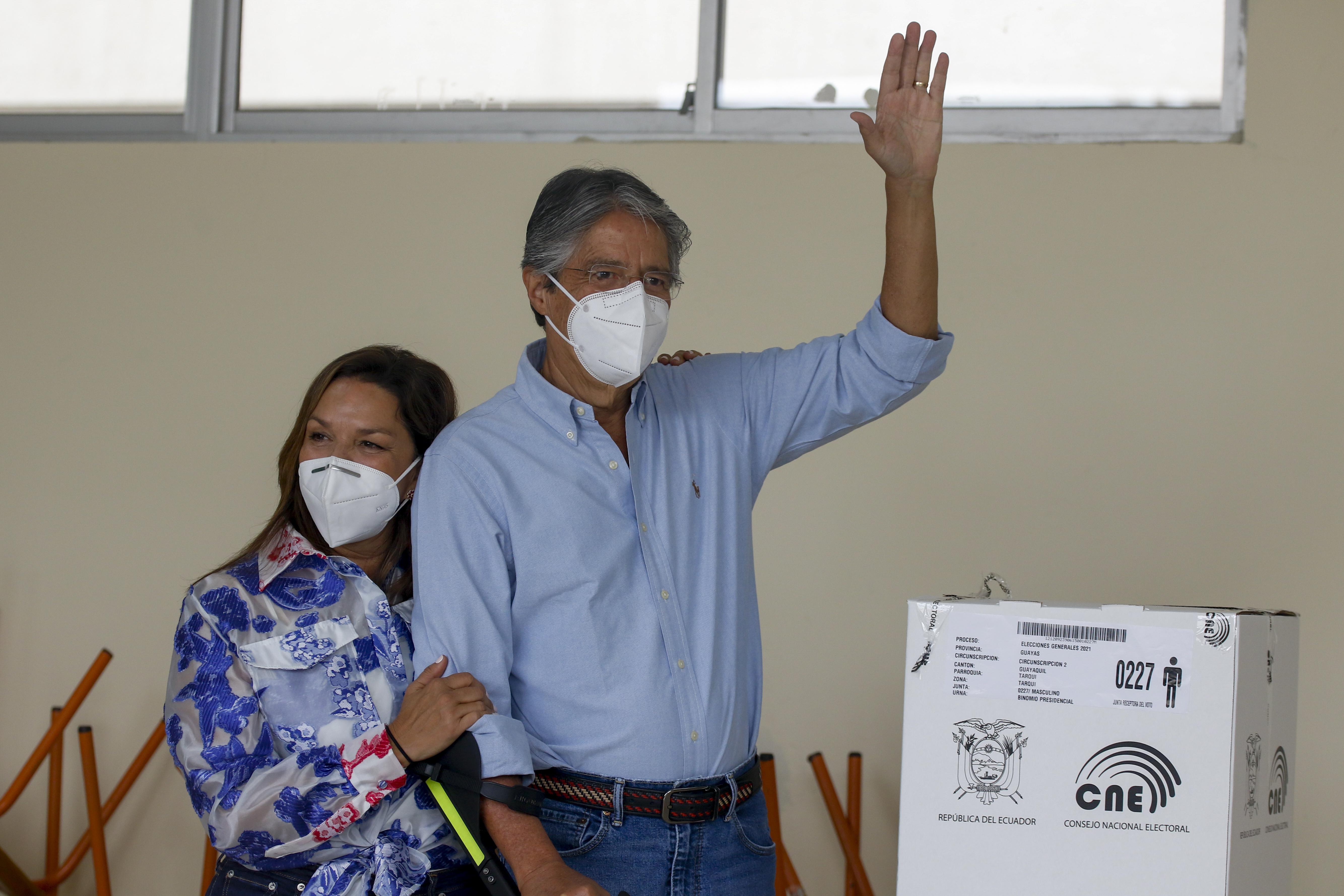 Guillermo Lasso saluda después de votar este domingo acompañado por su esposa.