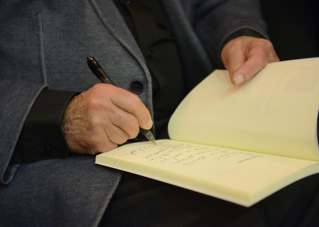 El poeta firmando uno de sus libros.