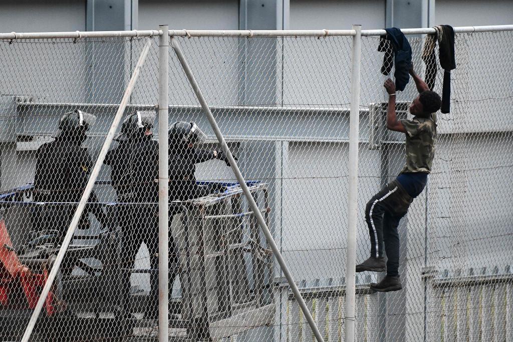 Un inmigrante es conminado a bajar de la valla fronteriza de Ceuta.