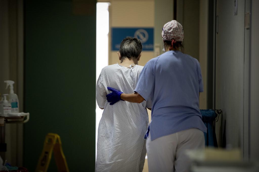 Una enfermera ayuda a un paciente con coronavirus.