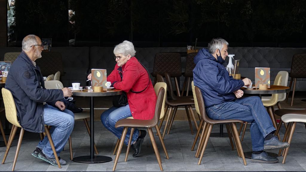 Una mujer fuma en una terraza de un restaurante.