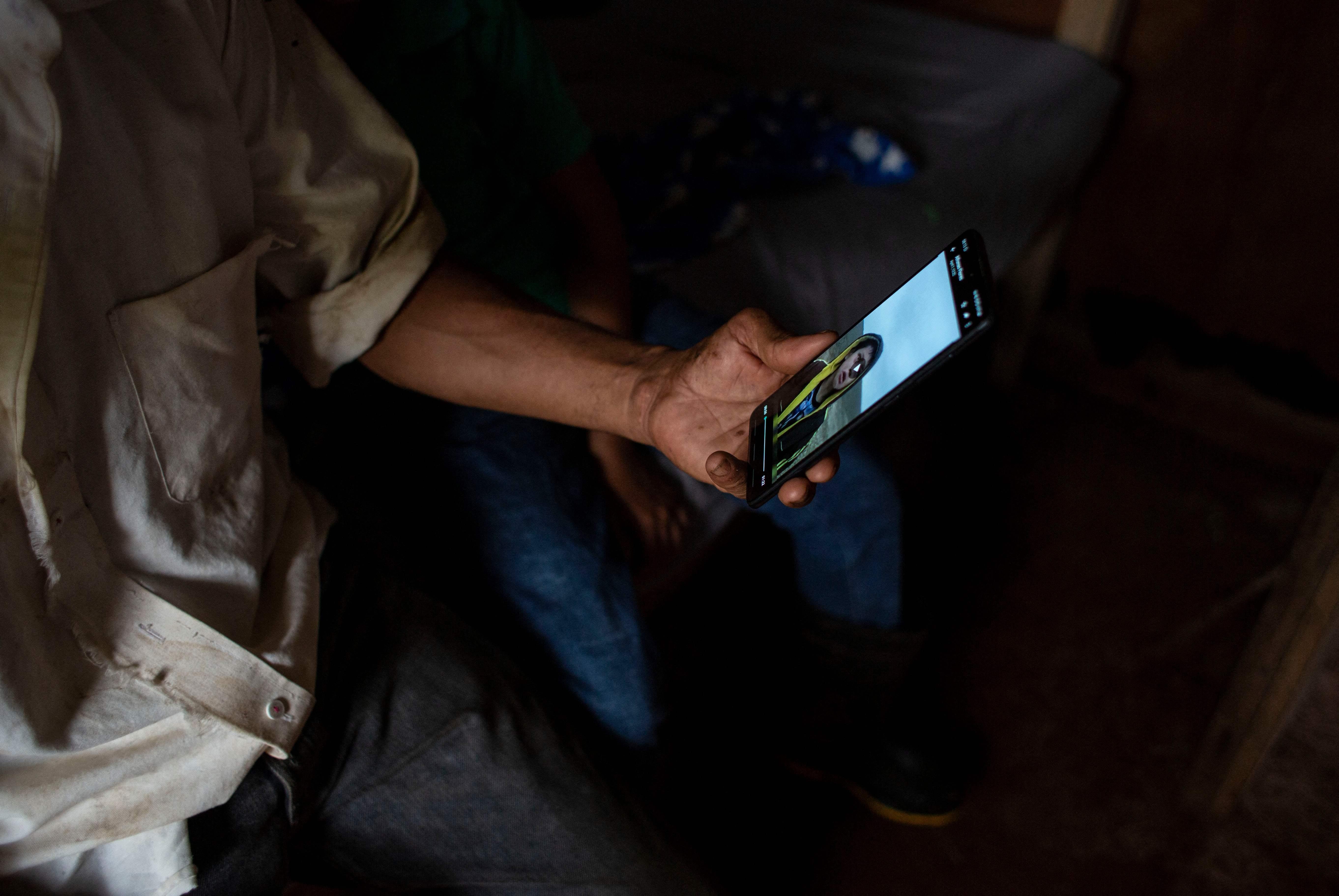 Lazaro Gutiérrez, padre del niño, viendo el vídeo de su hijo.