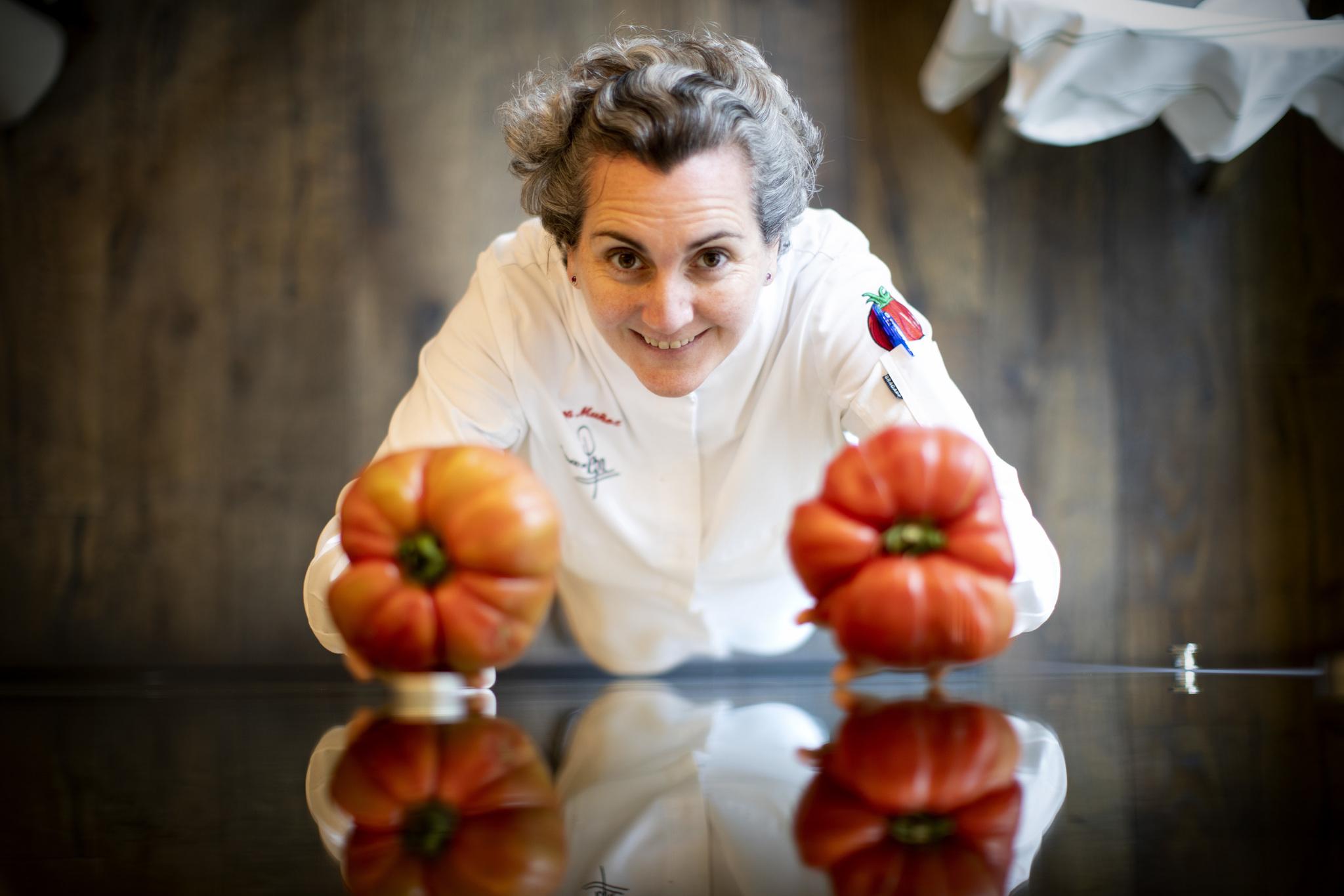Pepa Muñoz con dos de sus famosos tomates en su restaurante