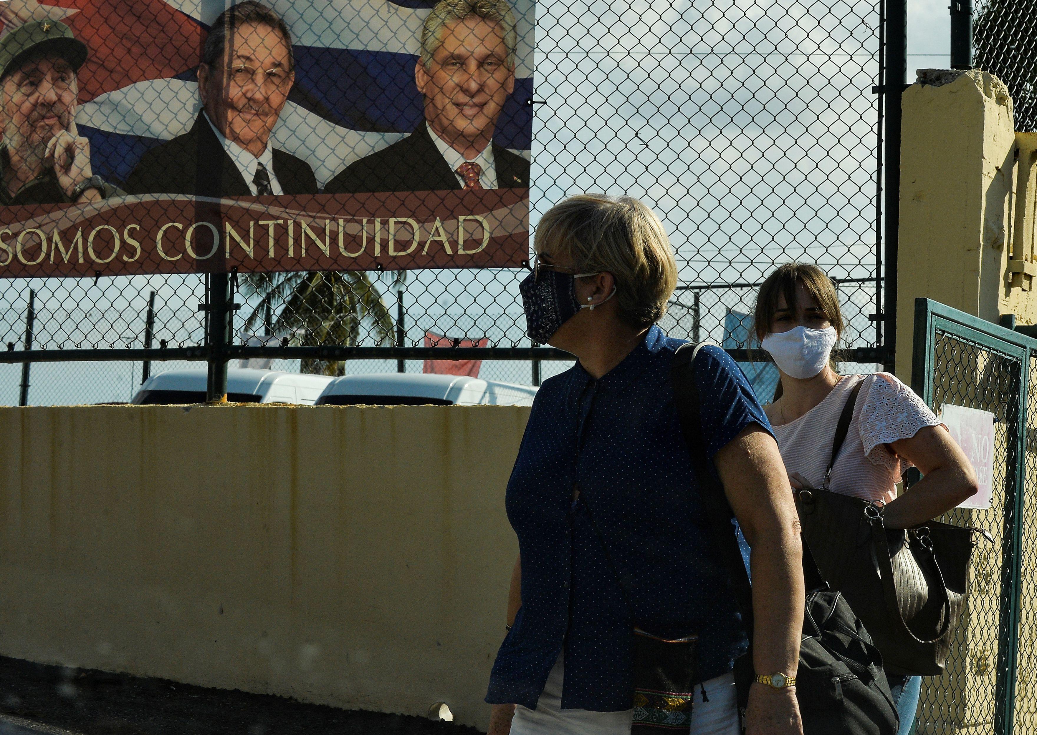 Dos mujeres caminan cerca de un cartel con Fidel y Raúl Castro junto al presidente Miguel Díaz Canel.