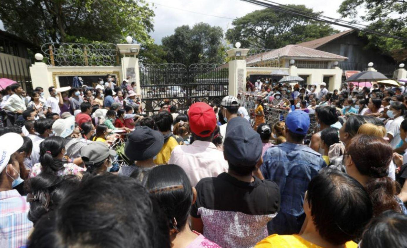 Familiares y amigos de los presos esperan su salida en la entrada de la prisión de Yangón.