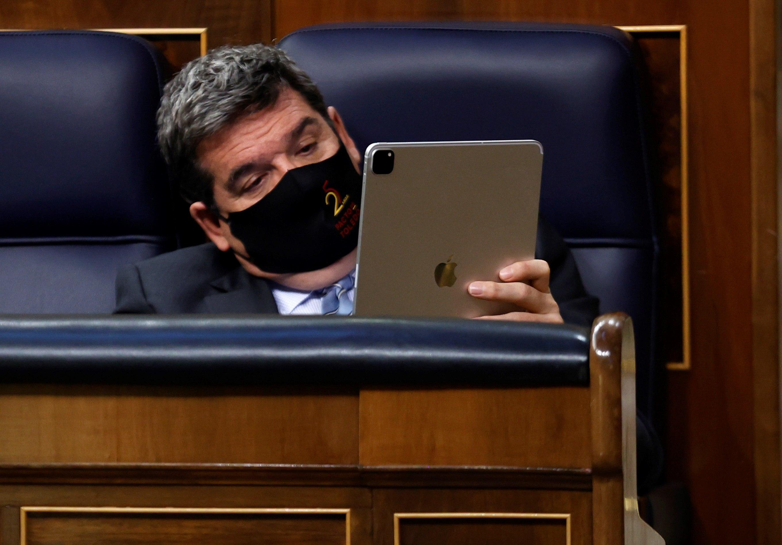 MADRID, 14/04/2021.- El ministro de Seguridad Social, José Luis Escrivá, revisa su tableta la semana pasada en el Congreso de los Diputados.
