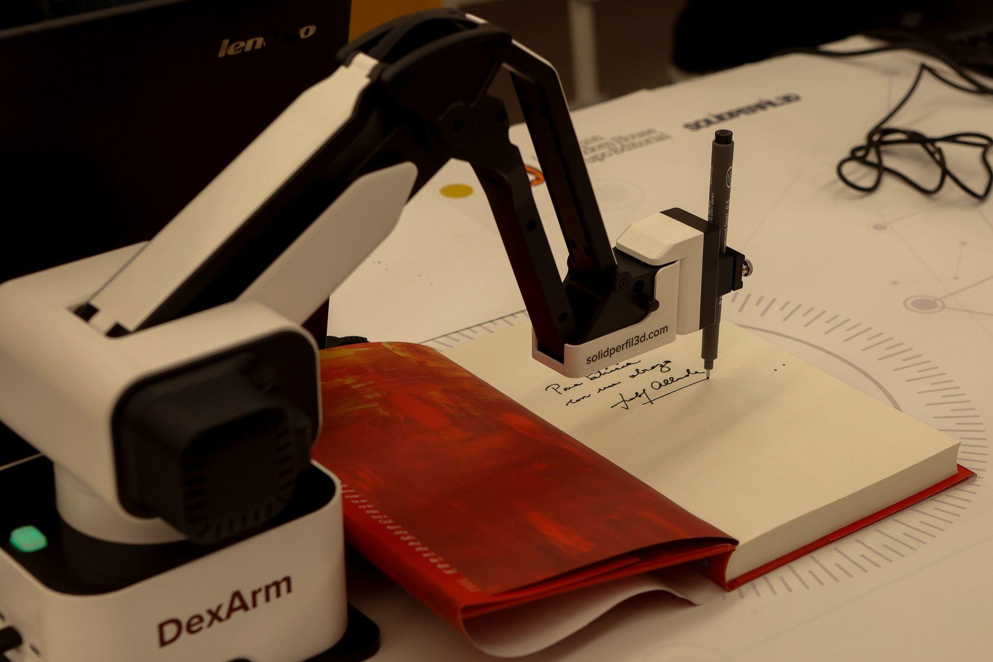 Un brazo robótico firma un libro de modo telemático.