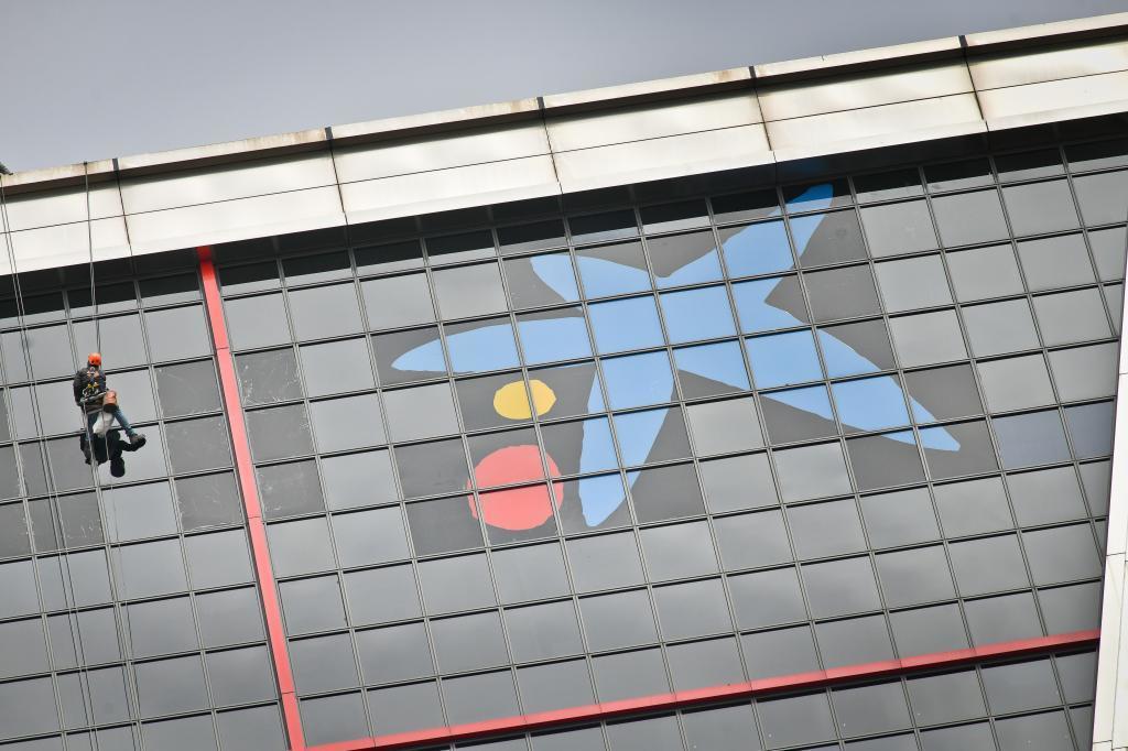 Un trabajador cambia el logo de Bankia por el de CaixaBank en las madrileñas Torres Kio.