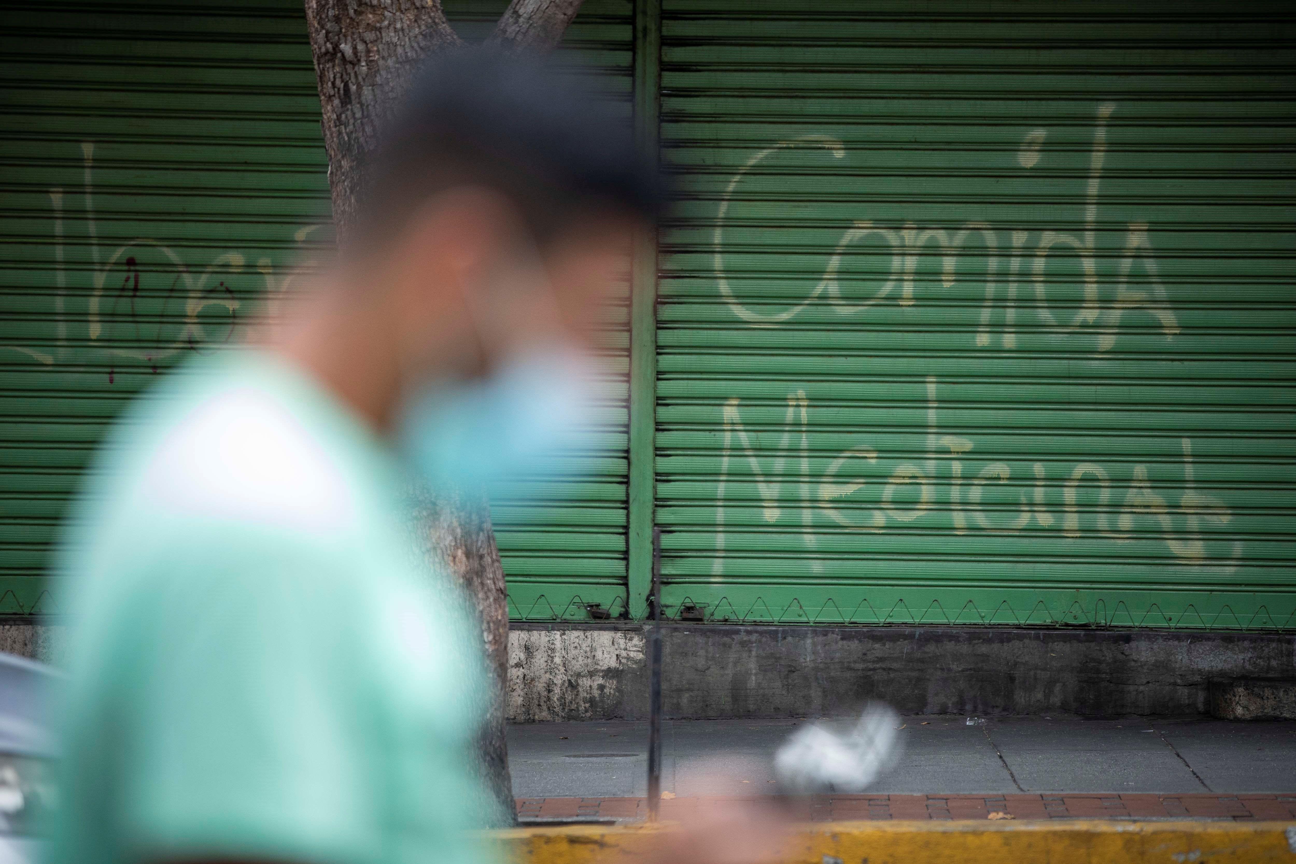 """Un hombre frente a un grafiti que dice """"comida, medicinal"""", en Caracas."""