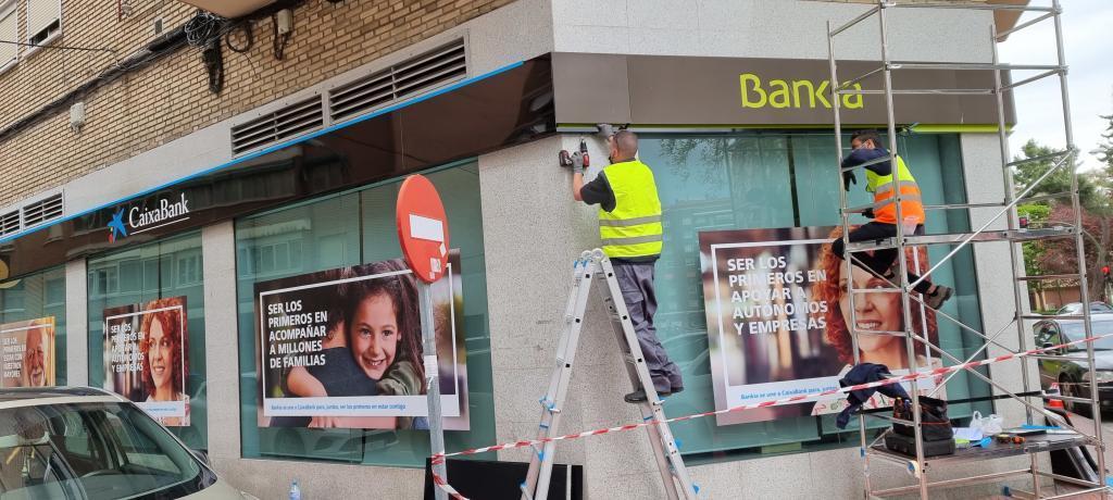 Unos operarios instalan el logo de CaixaBank en una antigua sucursal de Bankia.