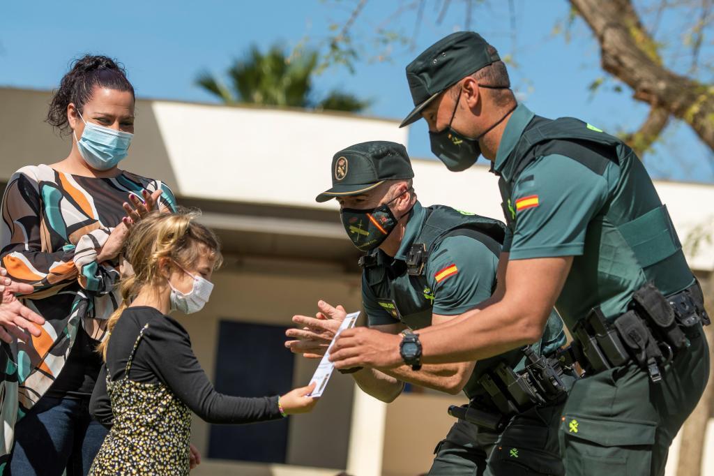 Los agentes Cuenca y Adame entregan a Alba un diploma por su comportamiento.