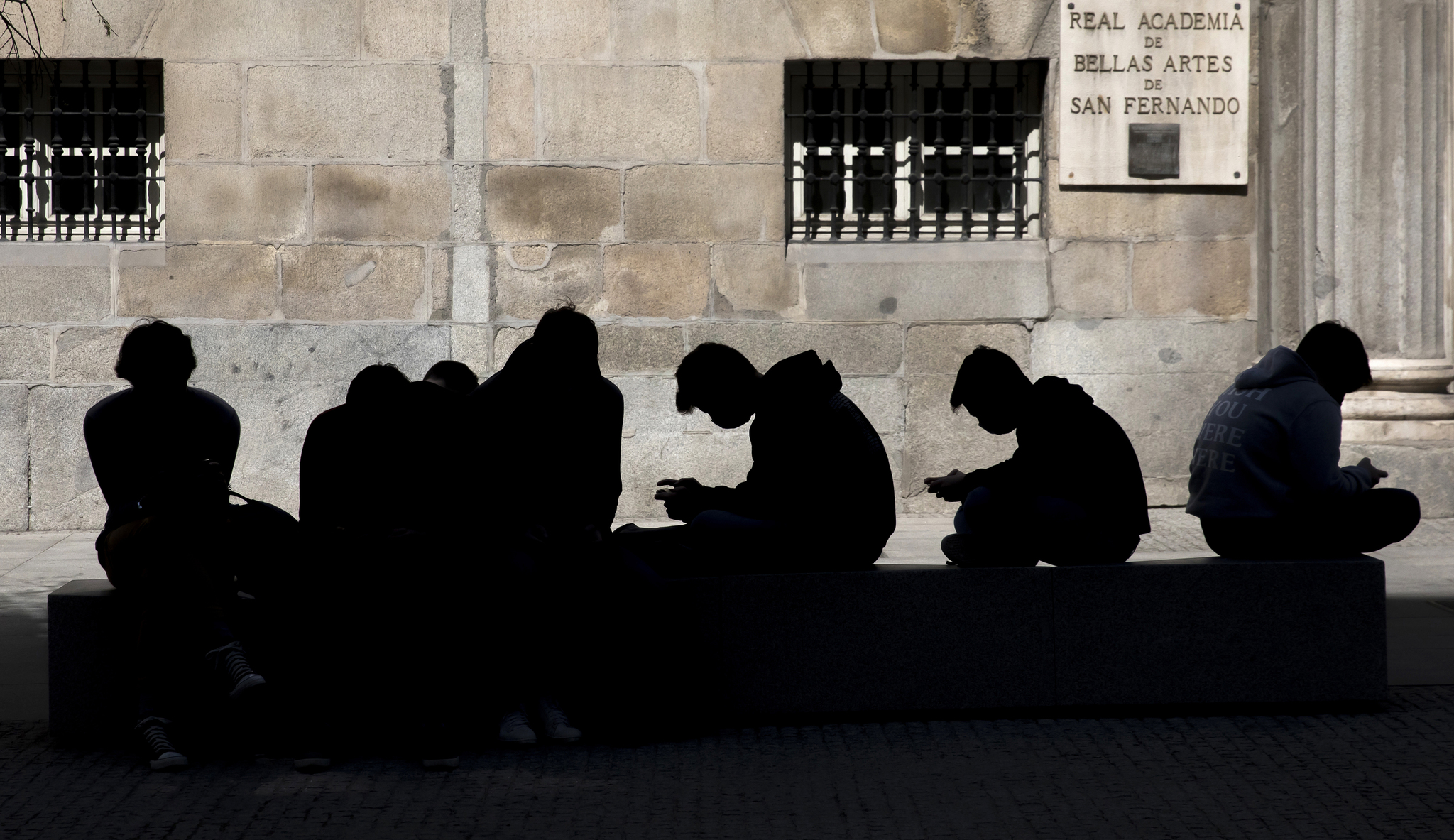 Un grupo de jóvenes, inmerso en la consulta de sus móviles.