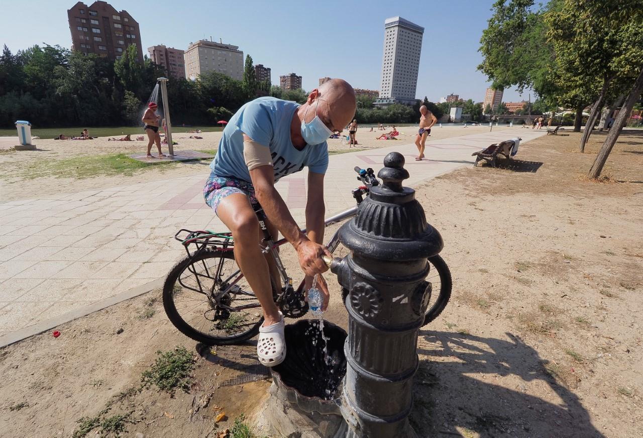 Un ciclista se refresca en la playa fluvial de Las Moreras de Valladolid