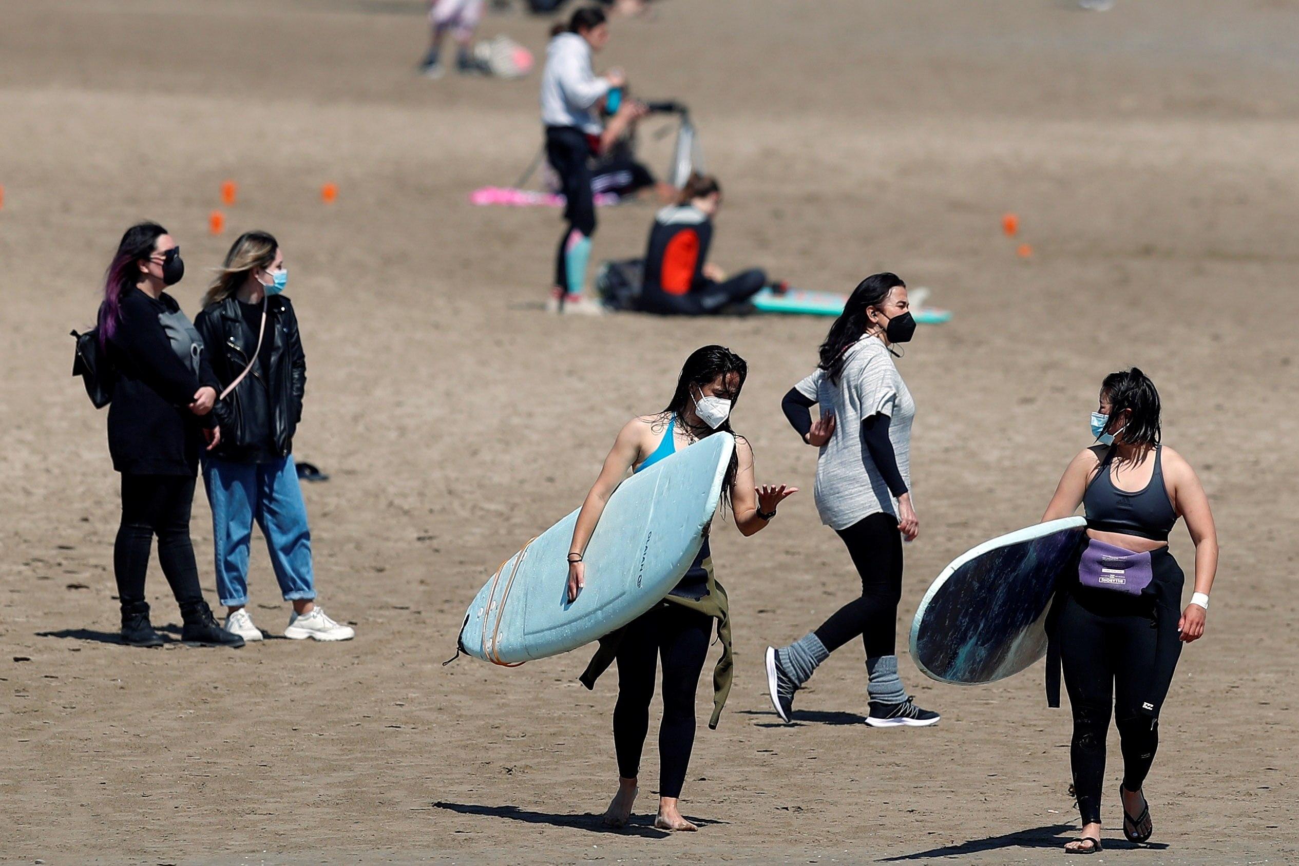 Un grupo de jóvenes disfruta de la playa de la Malvarrosa llevando mascarillas.