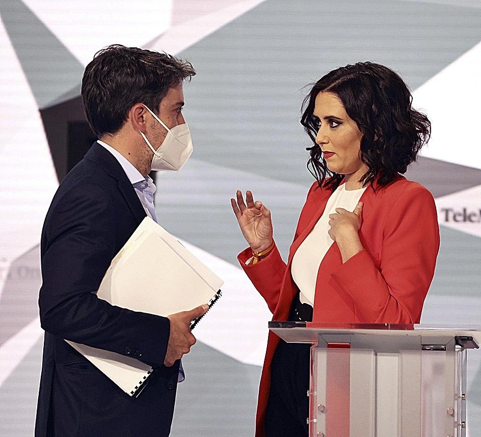 Isabel Díaz Ayuso conversa con su asesor antes del inicio del debate, anoche.