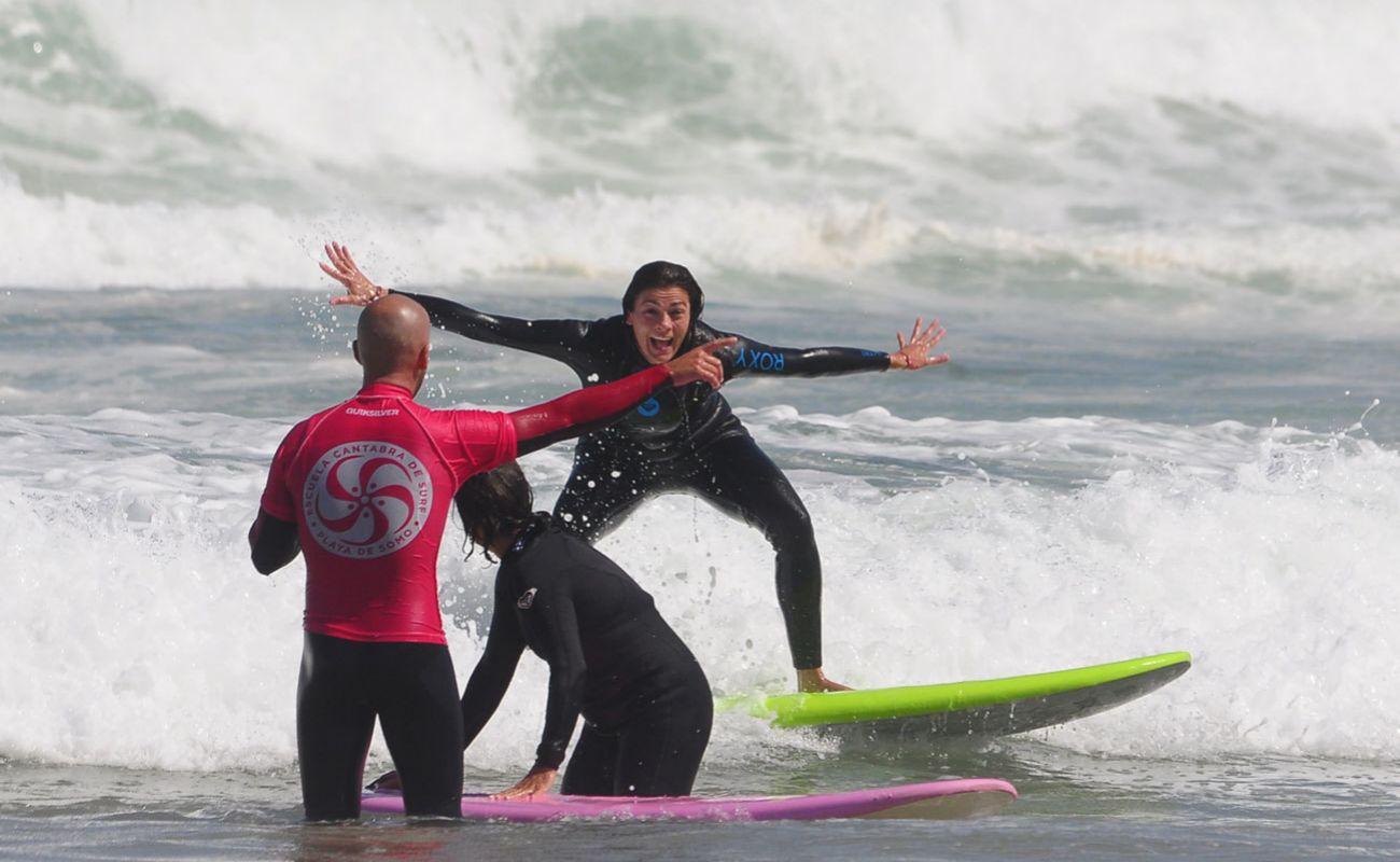 Un monitor de la Escuela Cántabra de Surf dando instrucciones a una alumna.