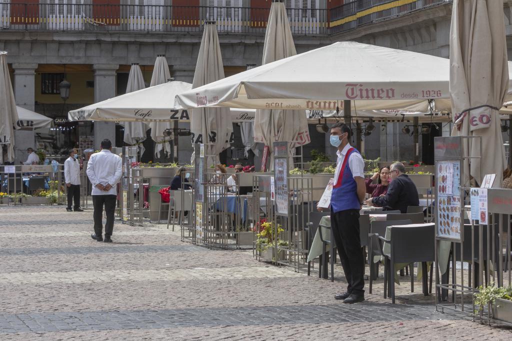 Camareros a la espera de comensales en terrazas ubicadas en la Plaza Mayor.