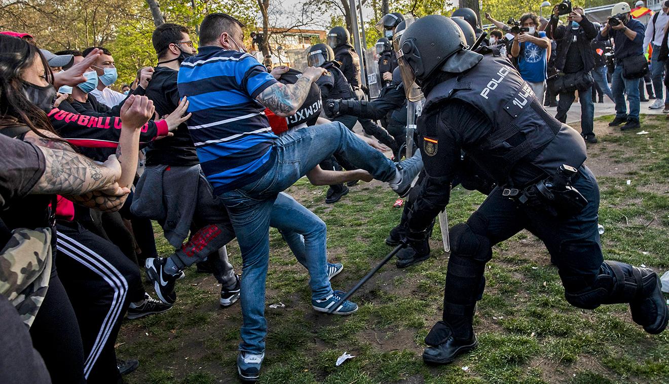 Los dos detenidos (uno con camisa negra y otro de rayas), durante los incidentes.