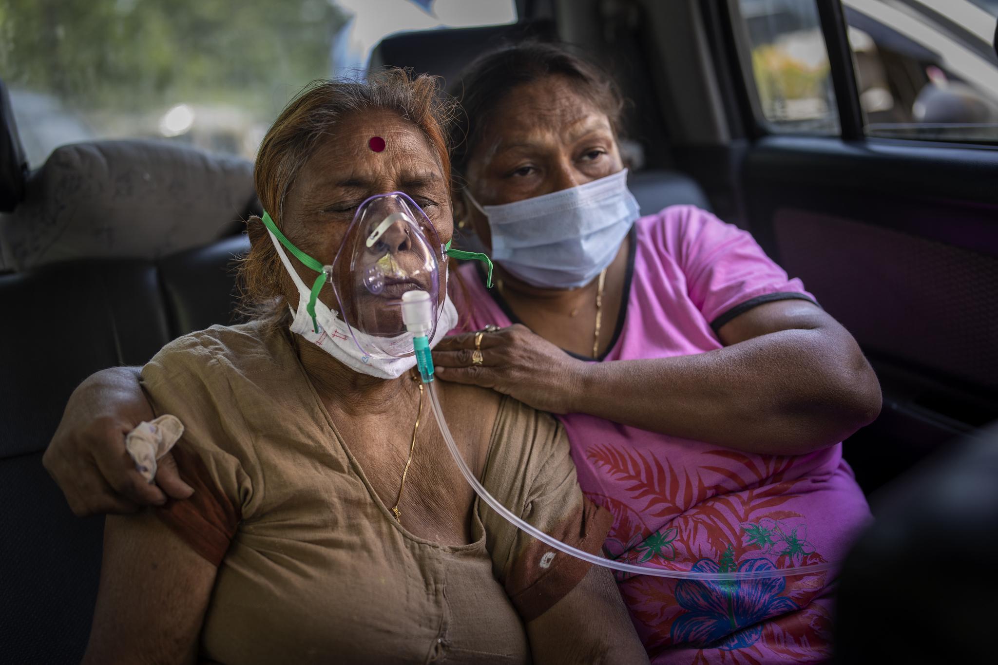 Una paciente es atendida en un coche, en Delhi.