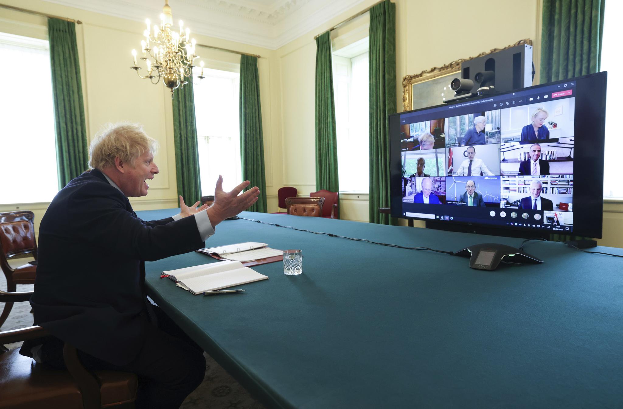 El primer ministro británico, Boris Johnson, en la reunión telemática del pasado viernes con una decena de dirigentes empresariales. En el centro, abajo, el presidente de Iberdrola, Ignacio Sánchez Galán