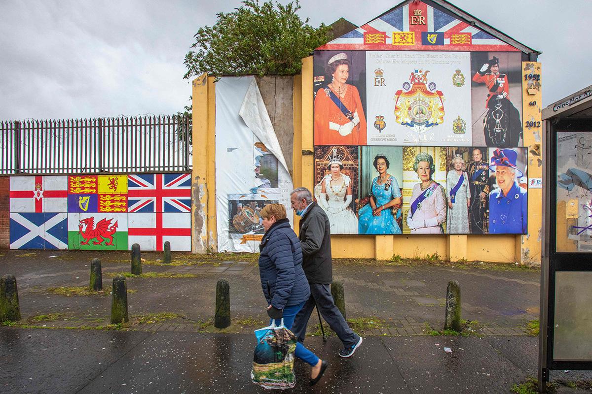 Dos habitantes de Belfast pasan ante un mural unionista sobre Isabel II.