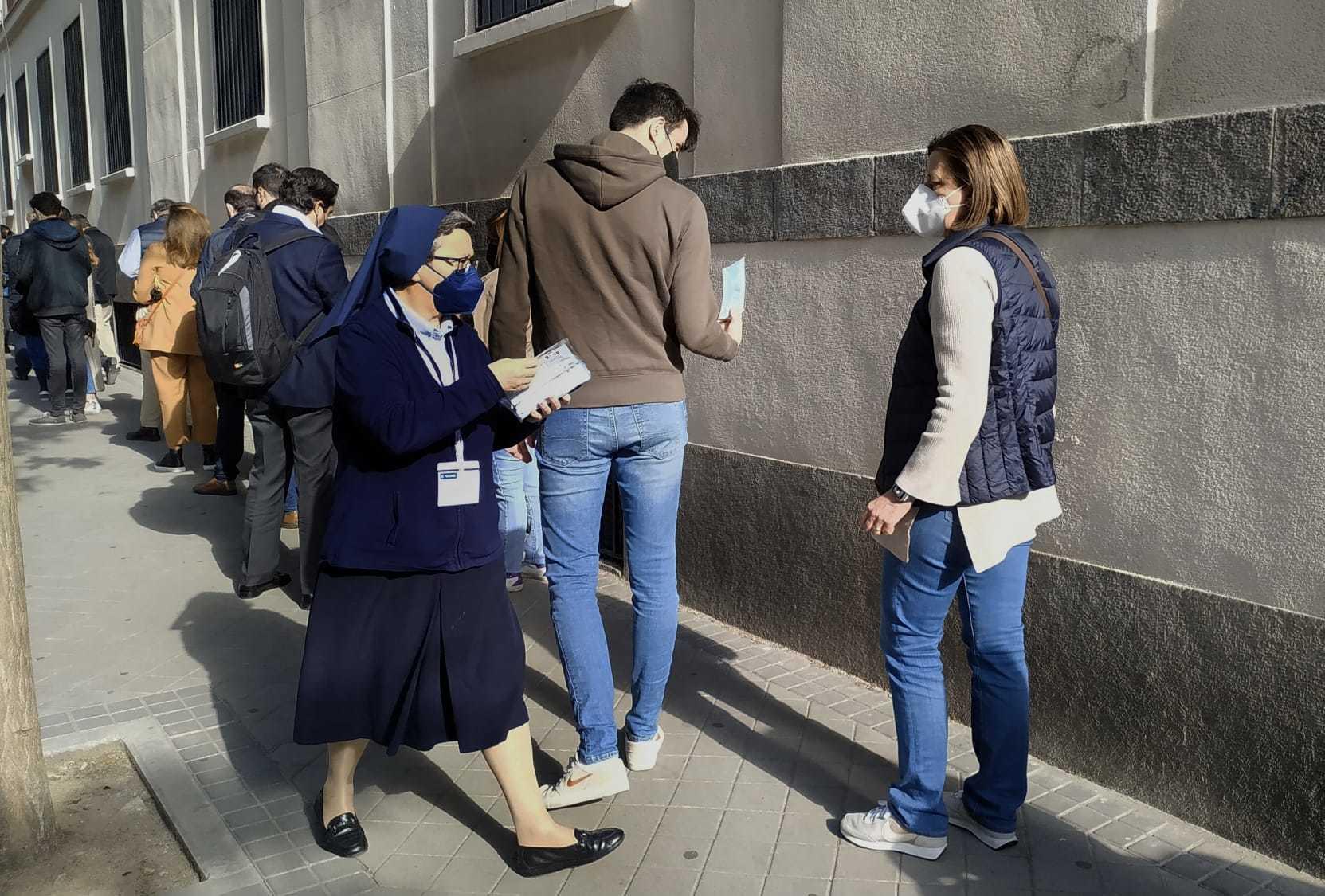 Mujer repartiendo mascarillas quirúrgicas en el colegio electoral La Inmaculada-Marillac.