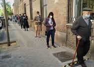 Madrileños haciendo cola en los colegios a primera hora.