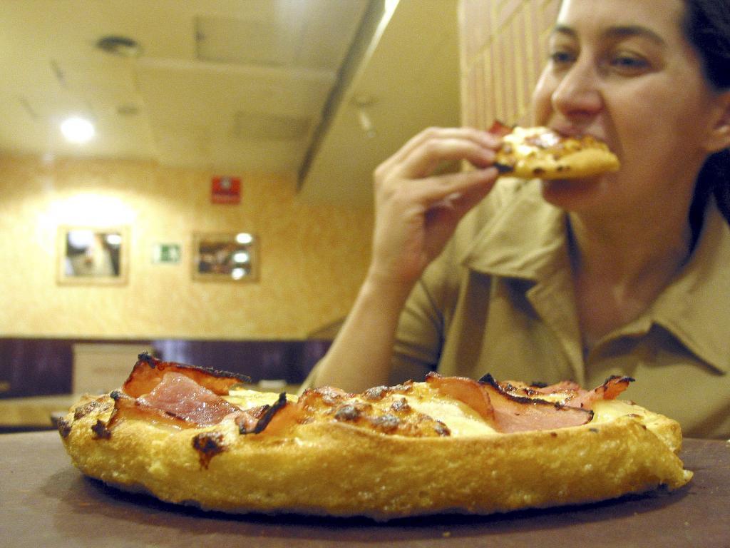 Una cliente se come una pizza en un local de Madrid