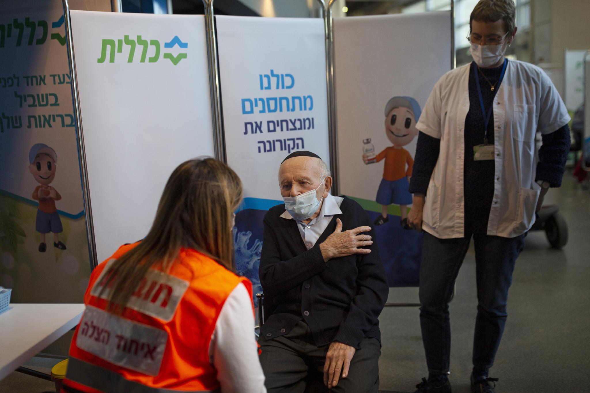 El superviviente del Holocausto, Joseph Zalman Kleinman, señala el brazo que prefiere para recibir la segunda dosis de la vacuna Pfizer, en Jerusalén.