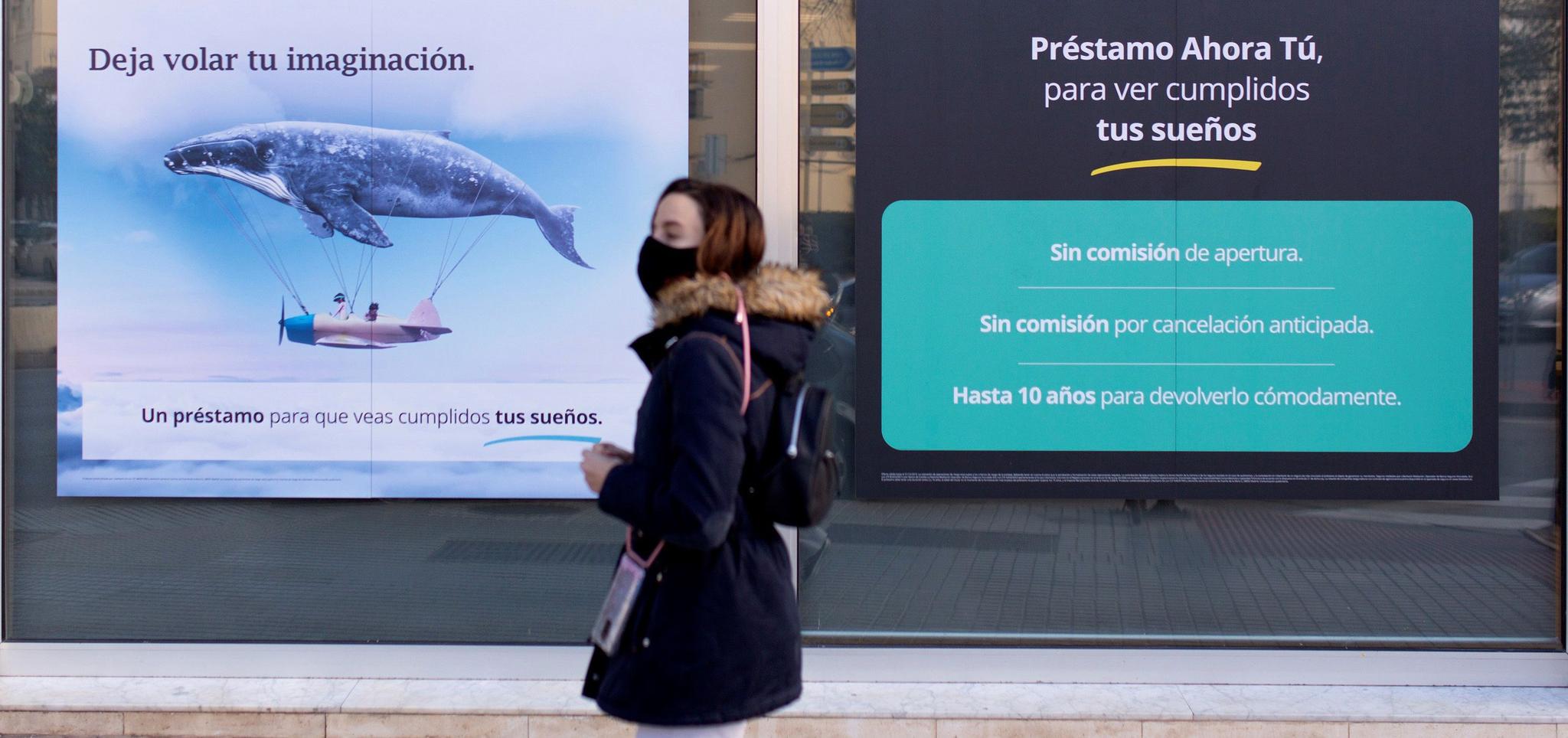 Una mujer pasea frente a los anuncios de una sucursal bancaria en Málaga.