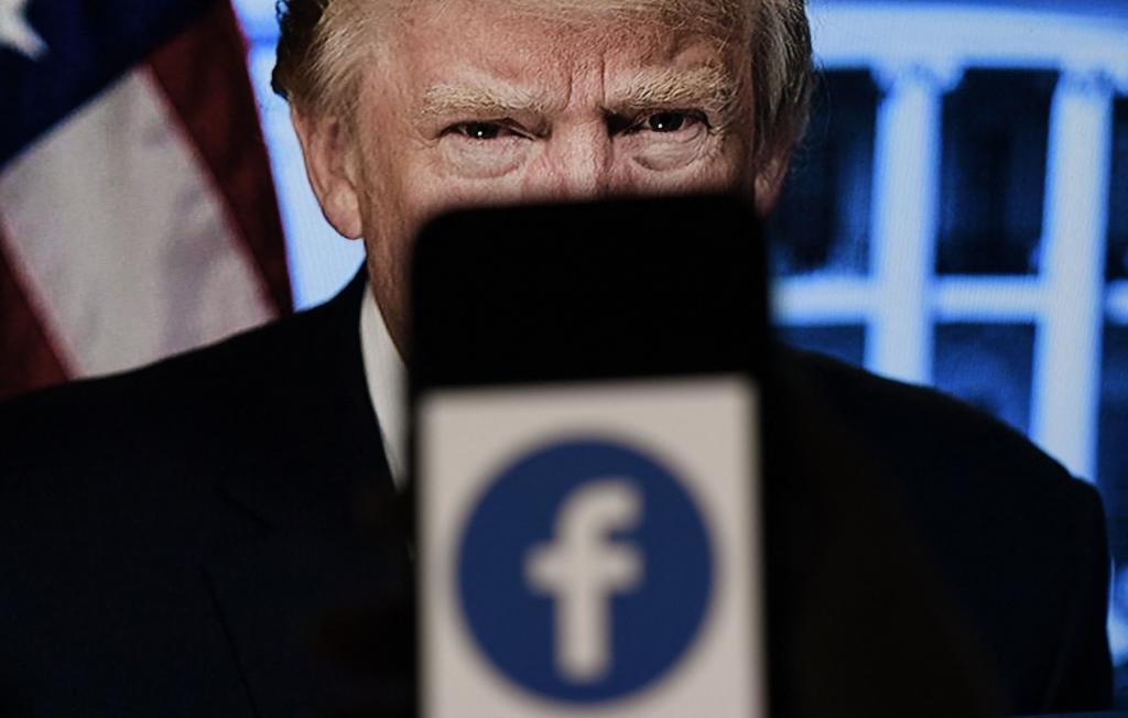Un smartphone muestra el logo de Facebook ante un fondo de Donald Trump
