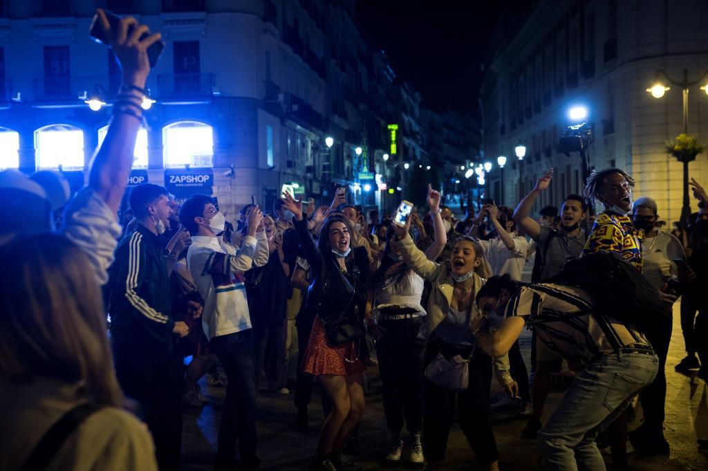 Jóvenes en Sol celebrando el fin del toque de queda, alguno de ellos sin mascarilla.