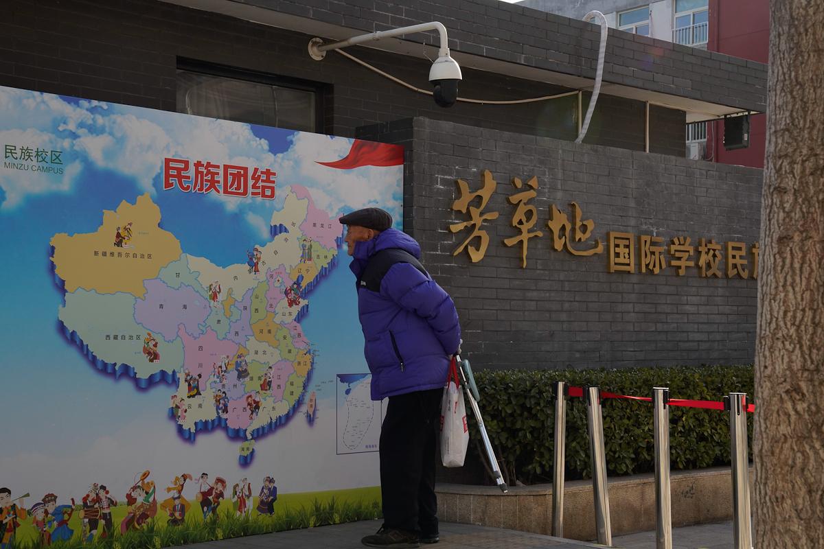 Un hombre mira un mapa étnico de China.