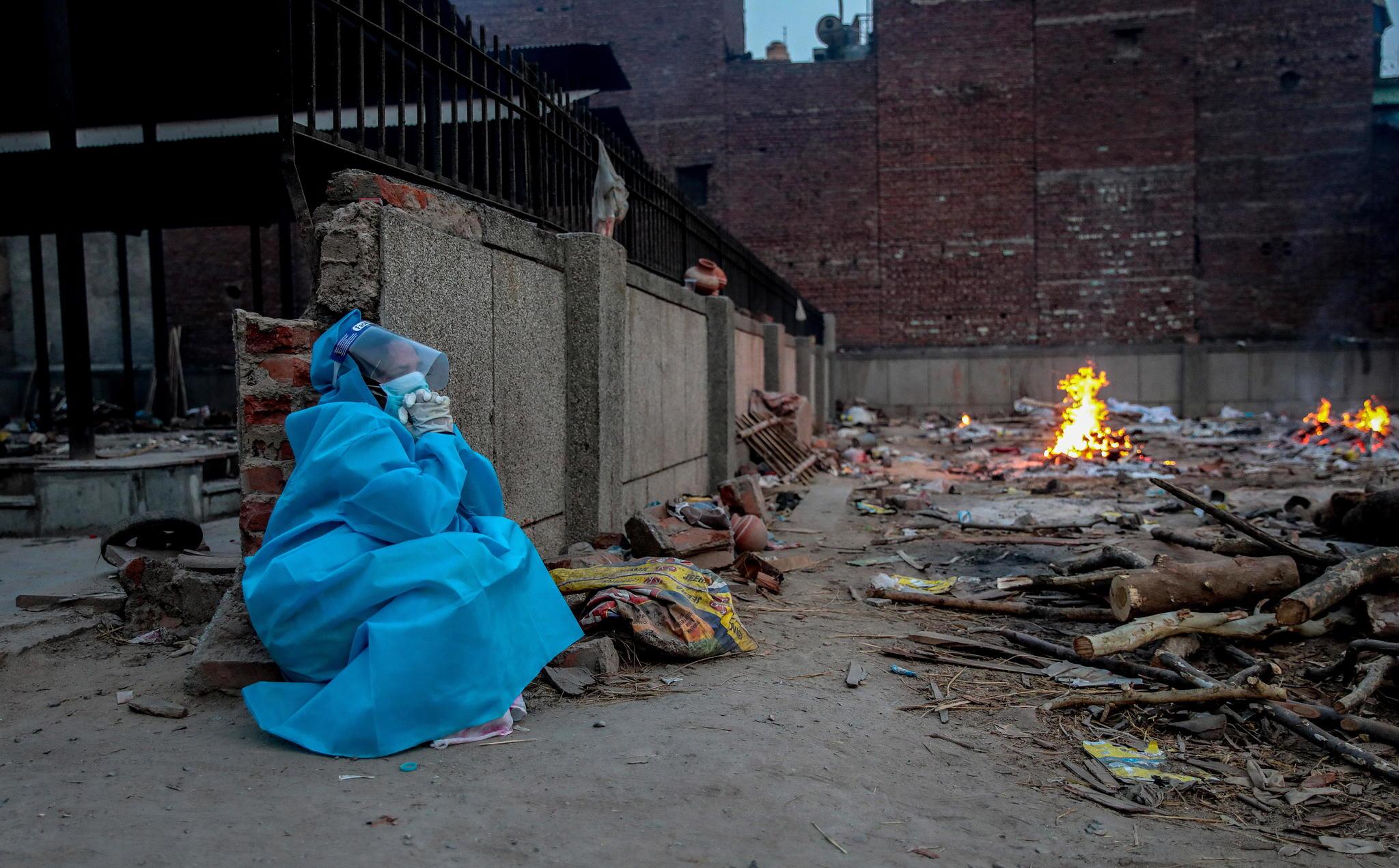 Una persona con EPI despide a un familiar en uno de los crematorios improvisados en Nueva Delhi (India).