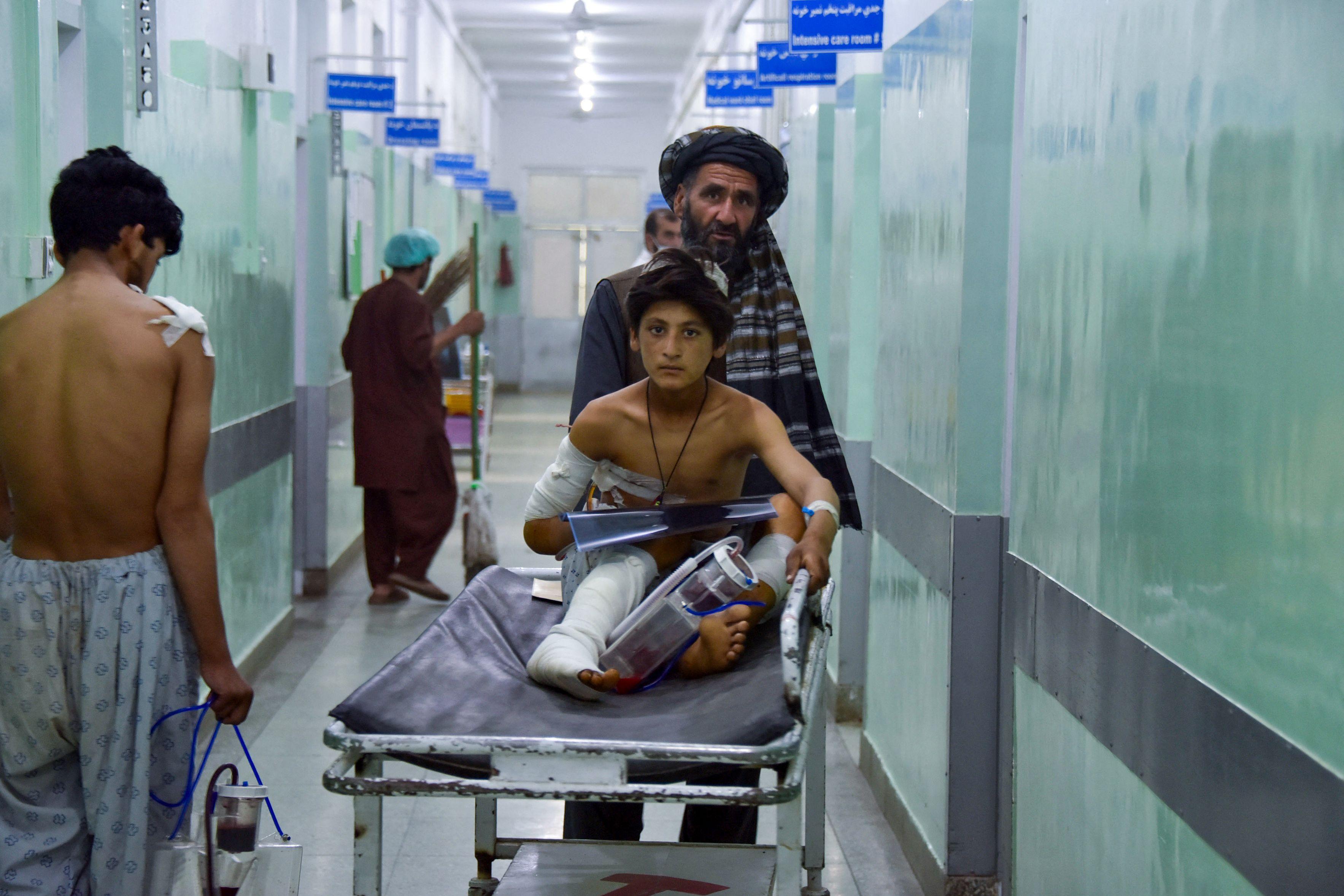 Un hombre traslada a uno de los heridos en el atentado, en un hospital en Kandahar.
