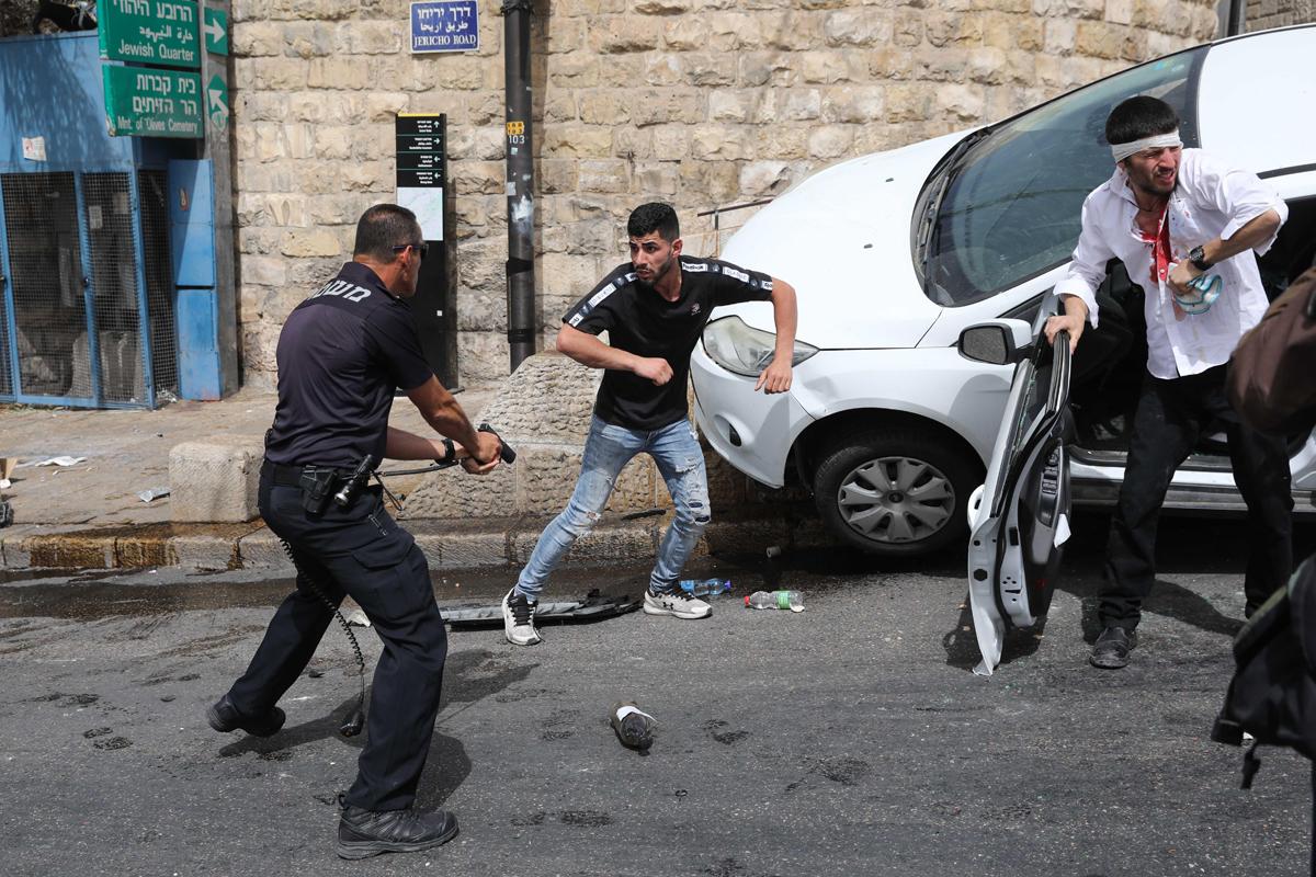 Un policía apunta con la pistola a un palestino que agredió con otros al conductor israelí en Jerusalén.