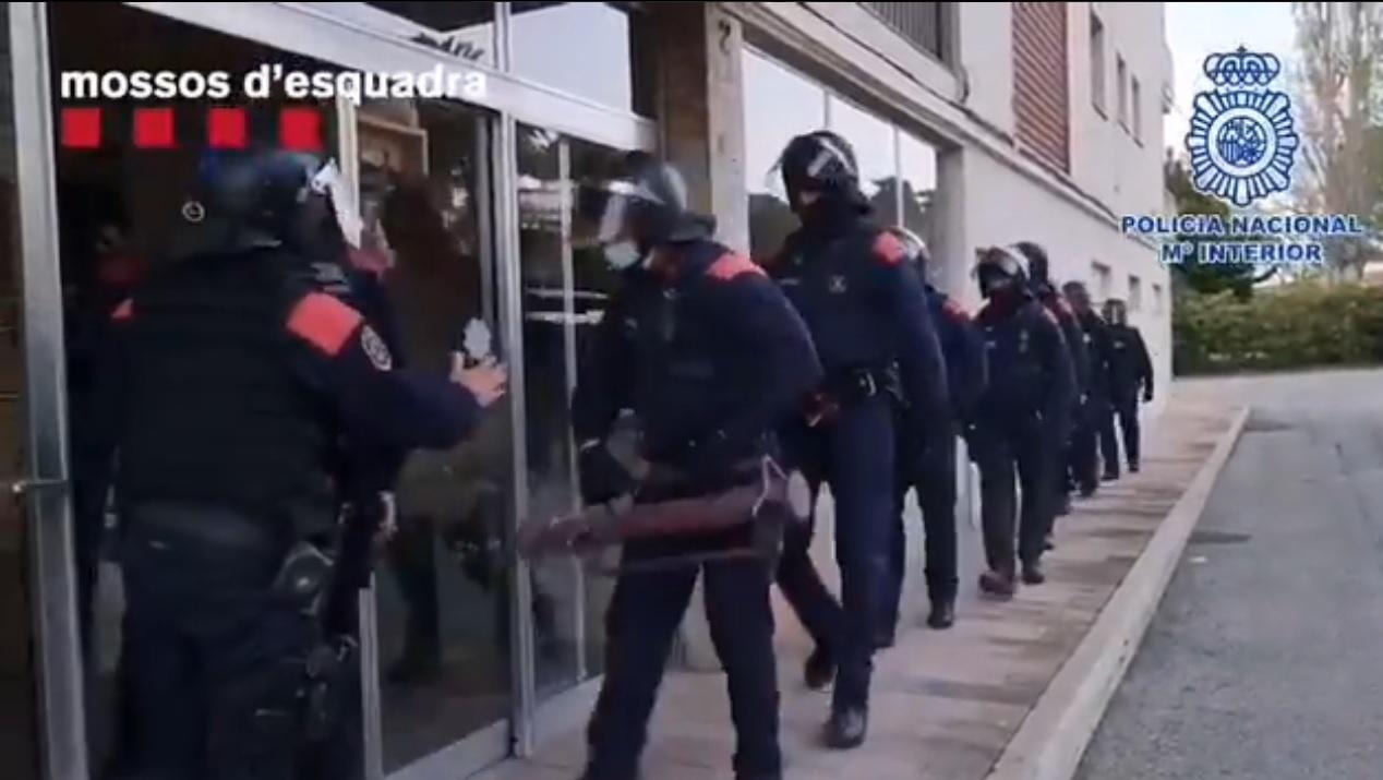Los Mossos d'esquadra acceden al interior de un establecimiento durante la operación.
