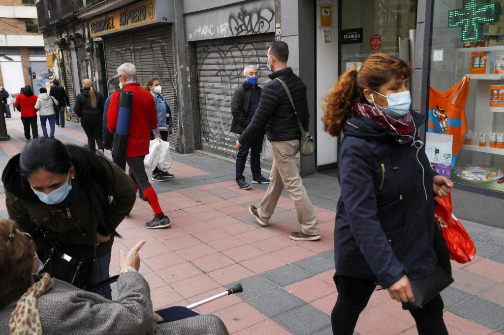 Paseantes con mascarilla en una calle de Madrid