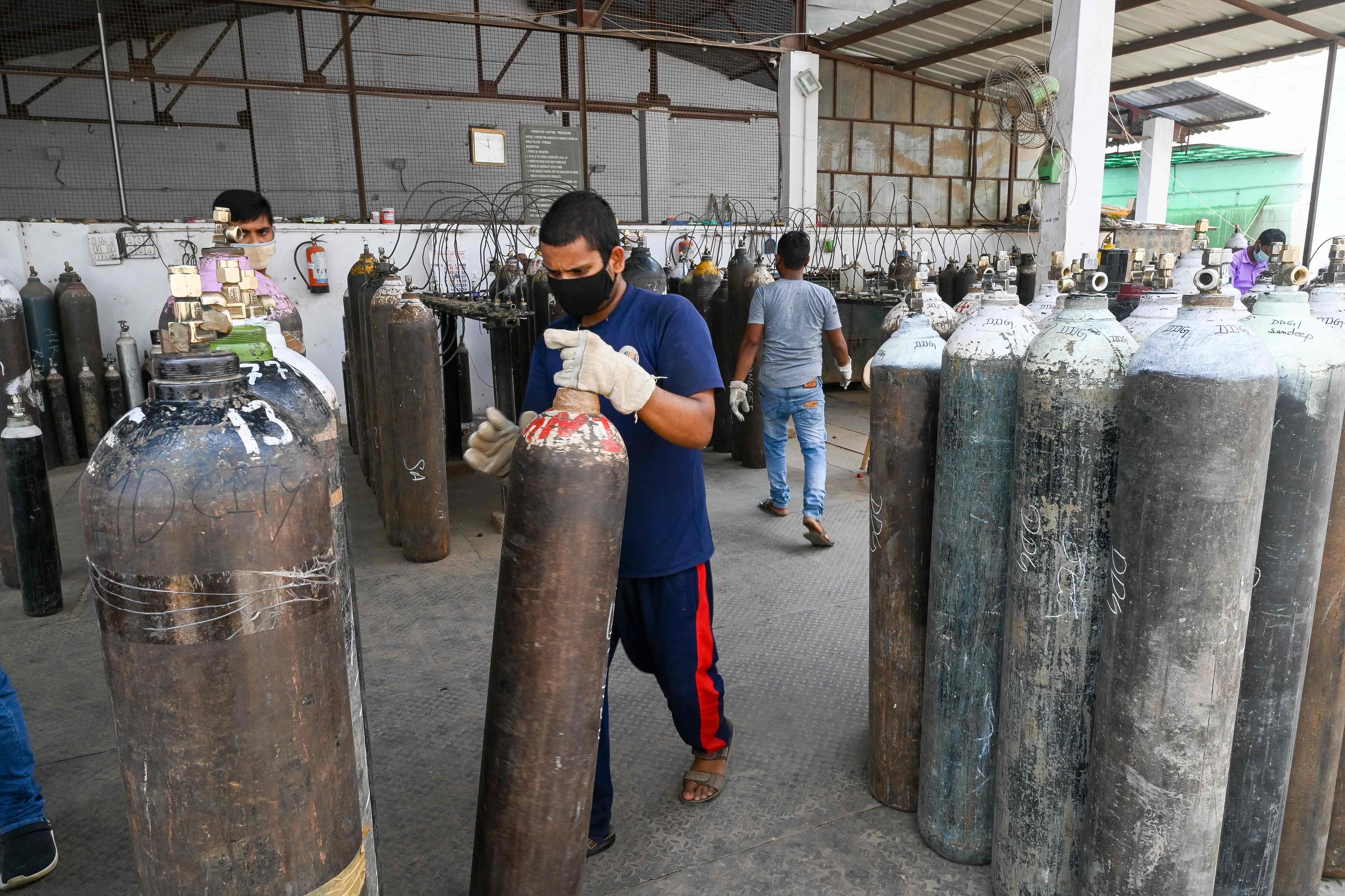 Un trabajador transporta bombonas de oxígeno para uso sanitario en Delhi.